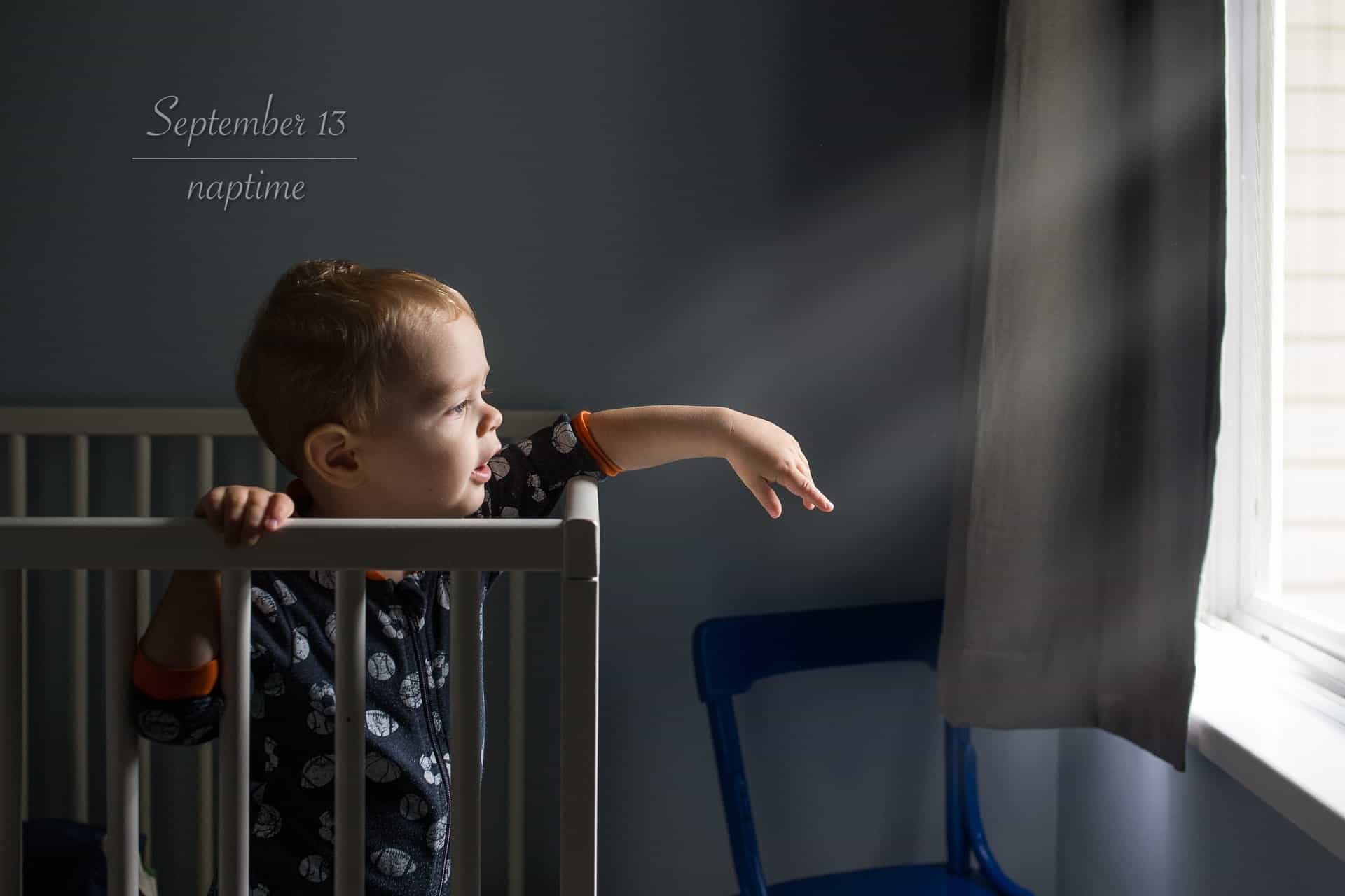 toddler boy reaching out towards light beams from his crib