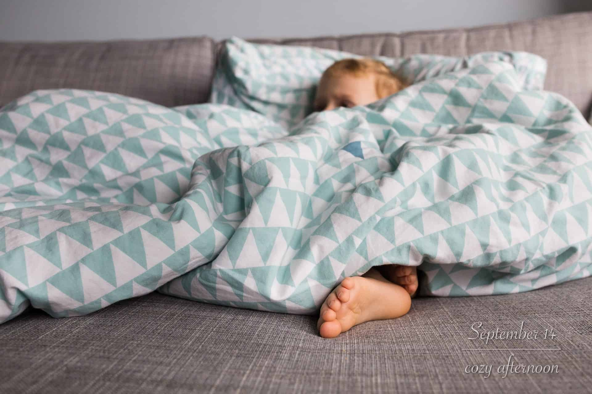 toddler boy laying on couch covered in blankets with foot sticking out