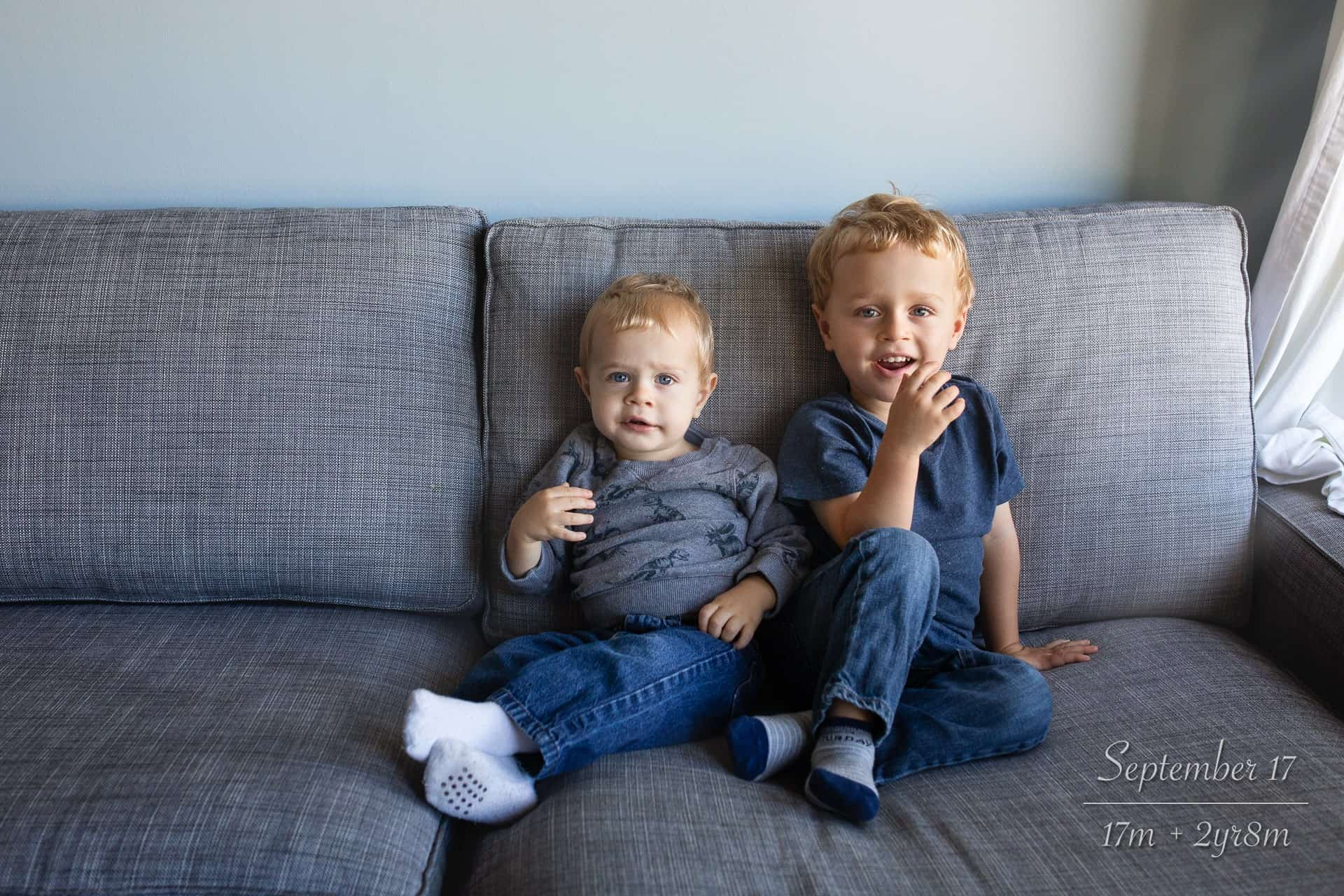 two brothers as toddlers sitting together on the couch