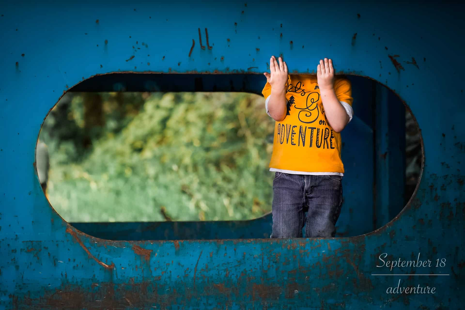 toddler boy wearing adventure shirt and hiding in playground