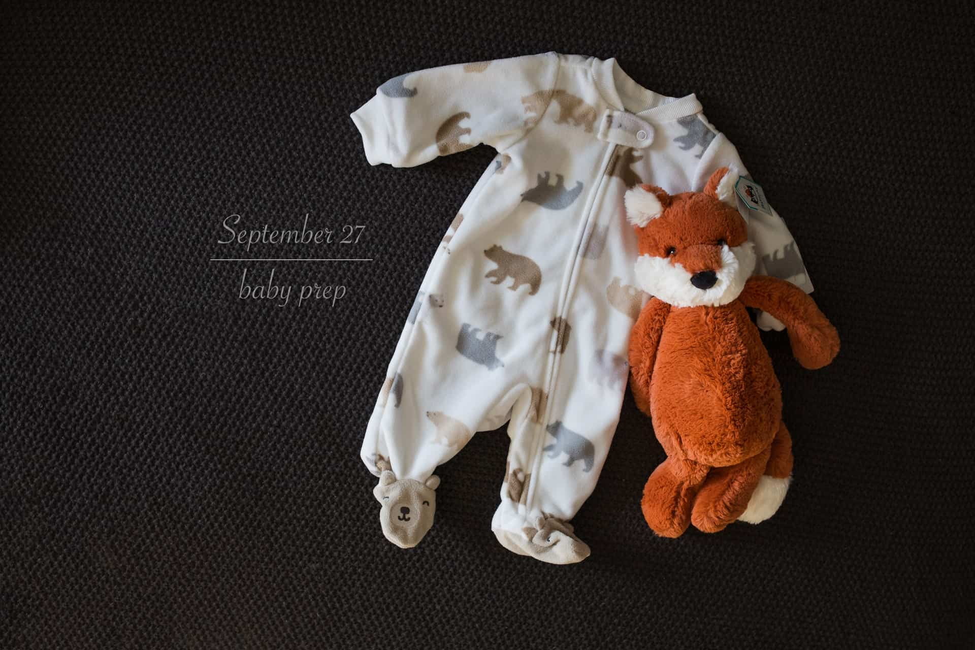 baby sleeper and stuffed fox laying on bed