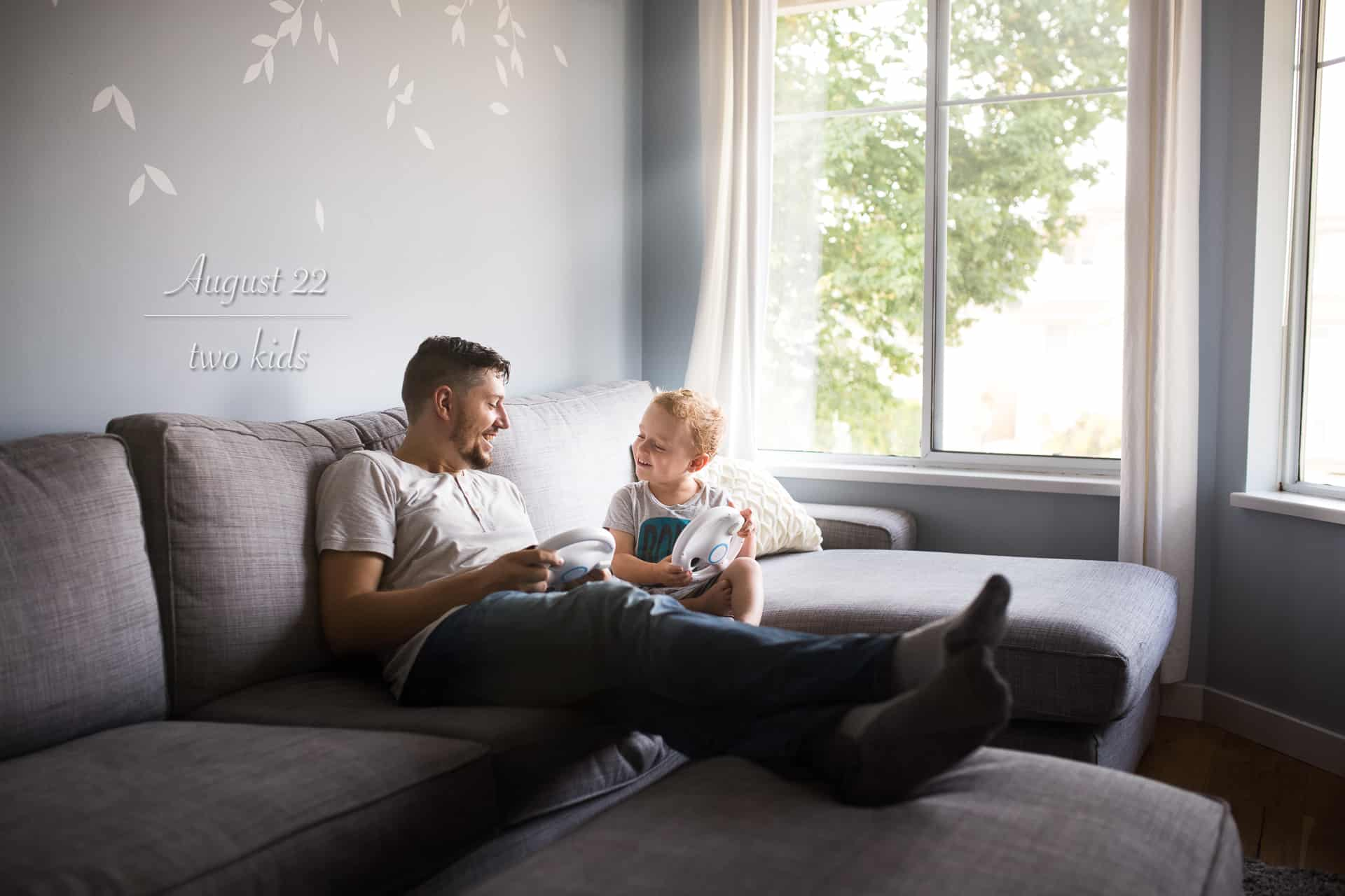 dad sitting on couch with toddler boy laughing and playing video games together
