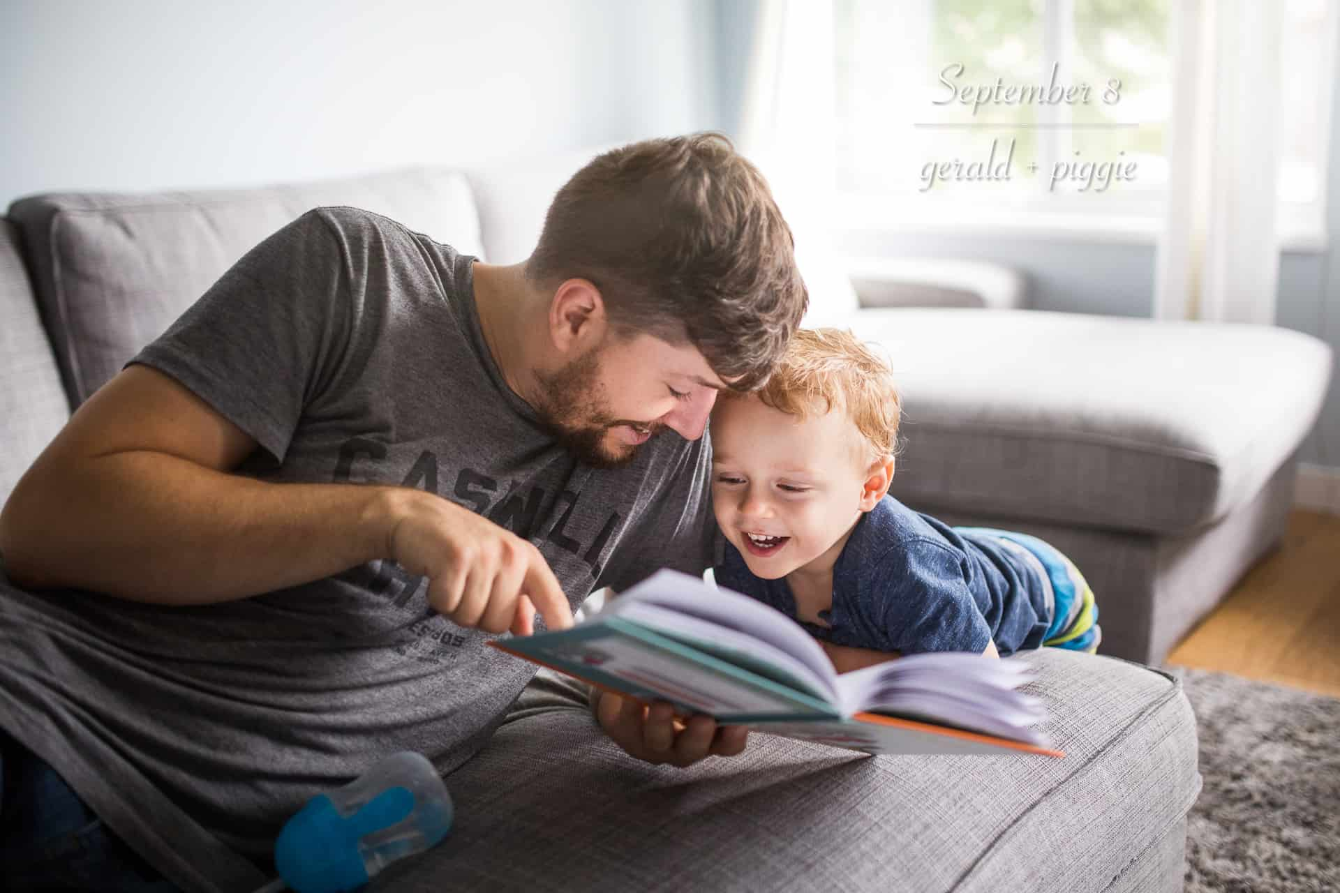 dad reading book to toddler boy who is laughing