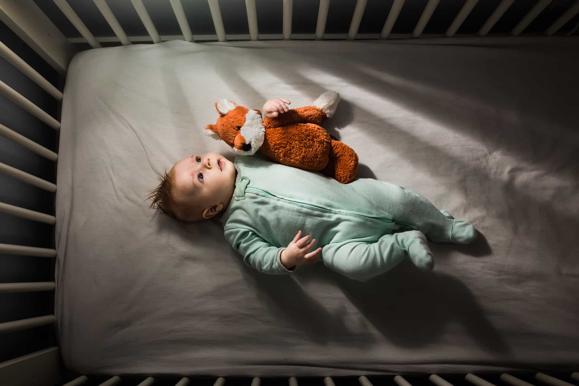 Baby boy in blue sleeper laying in crib with little fox