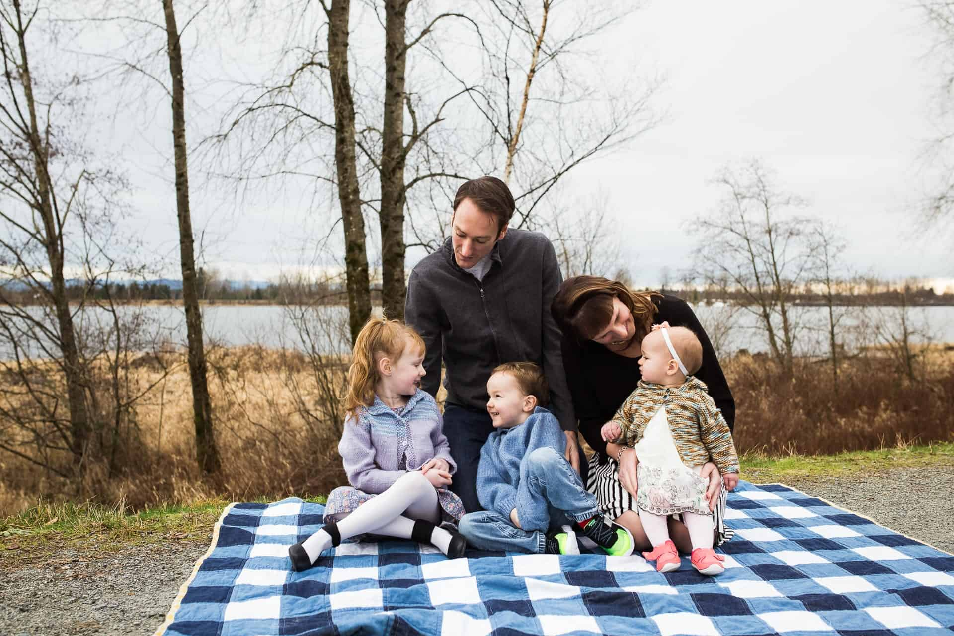Family of five on blanket by river laughing with each other