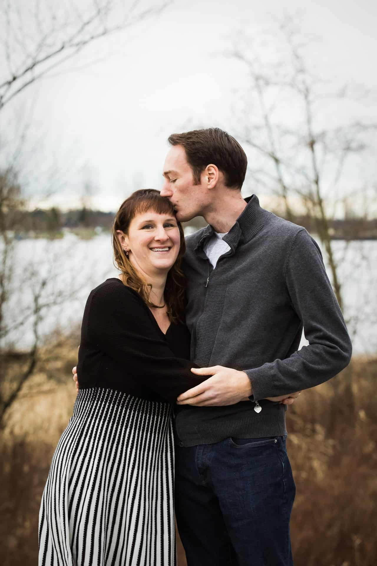 husband and wife by river with husband kissing wife's temple