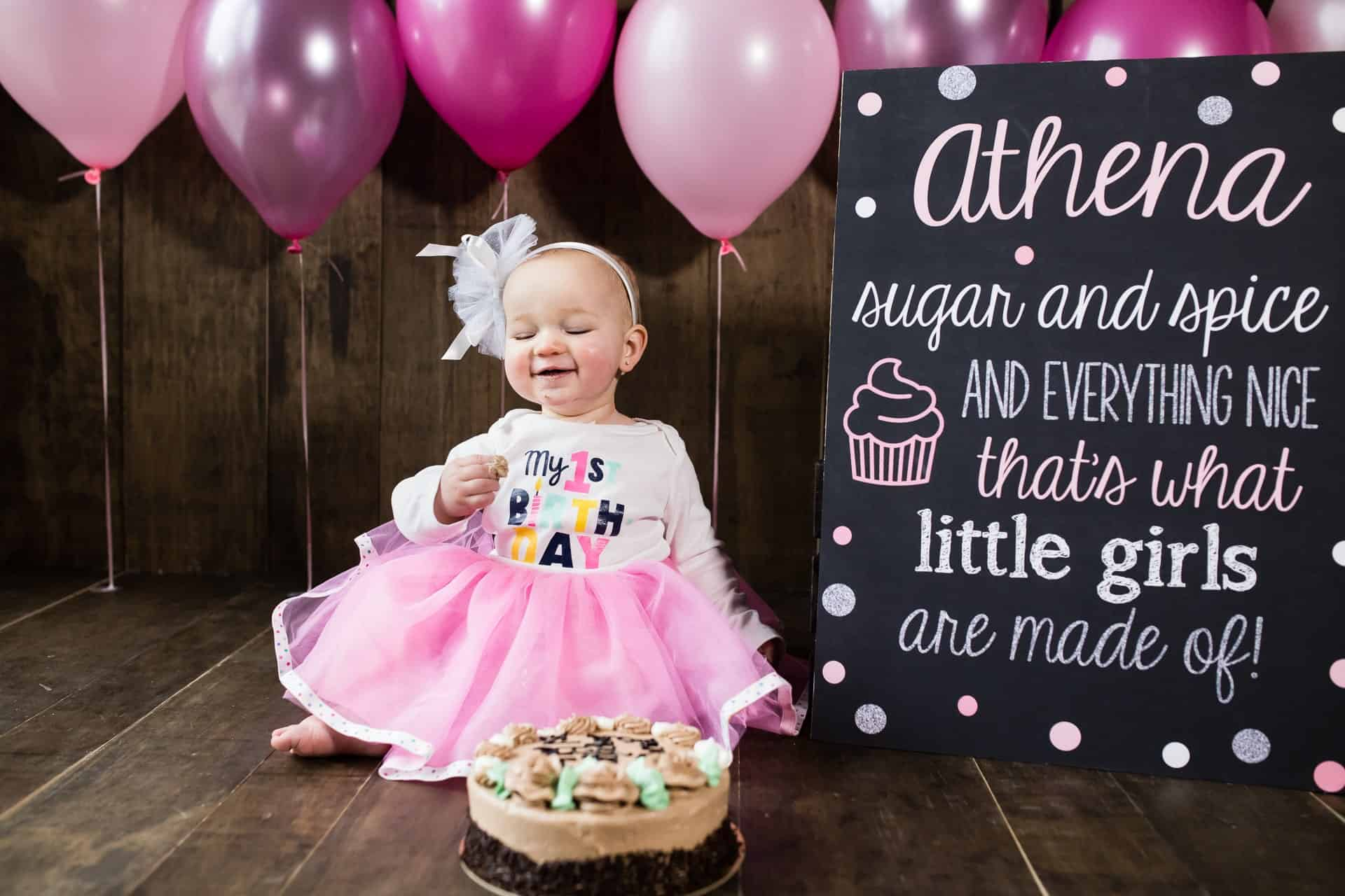 Little girl tasting her first birthday cake with pink balloons and sign