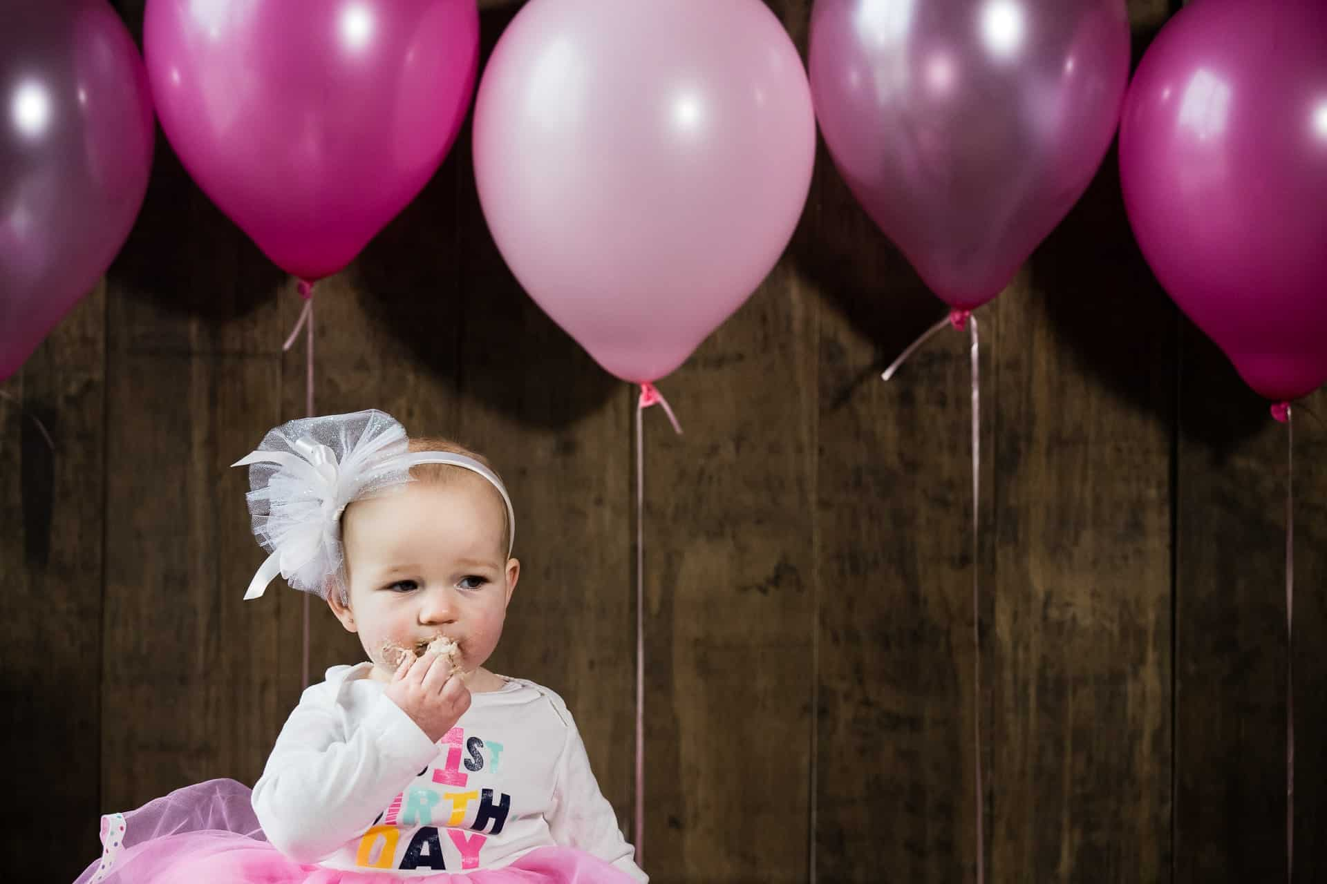 Little girl eating cake in front of pink balloons