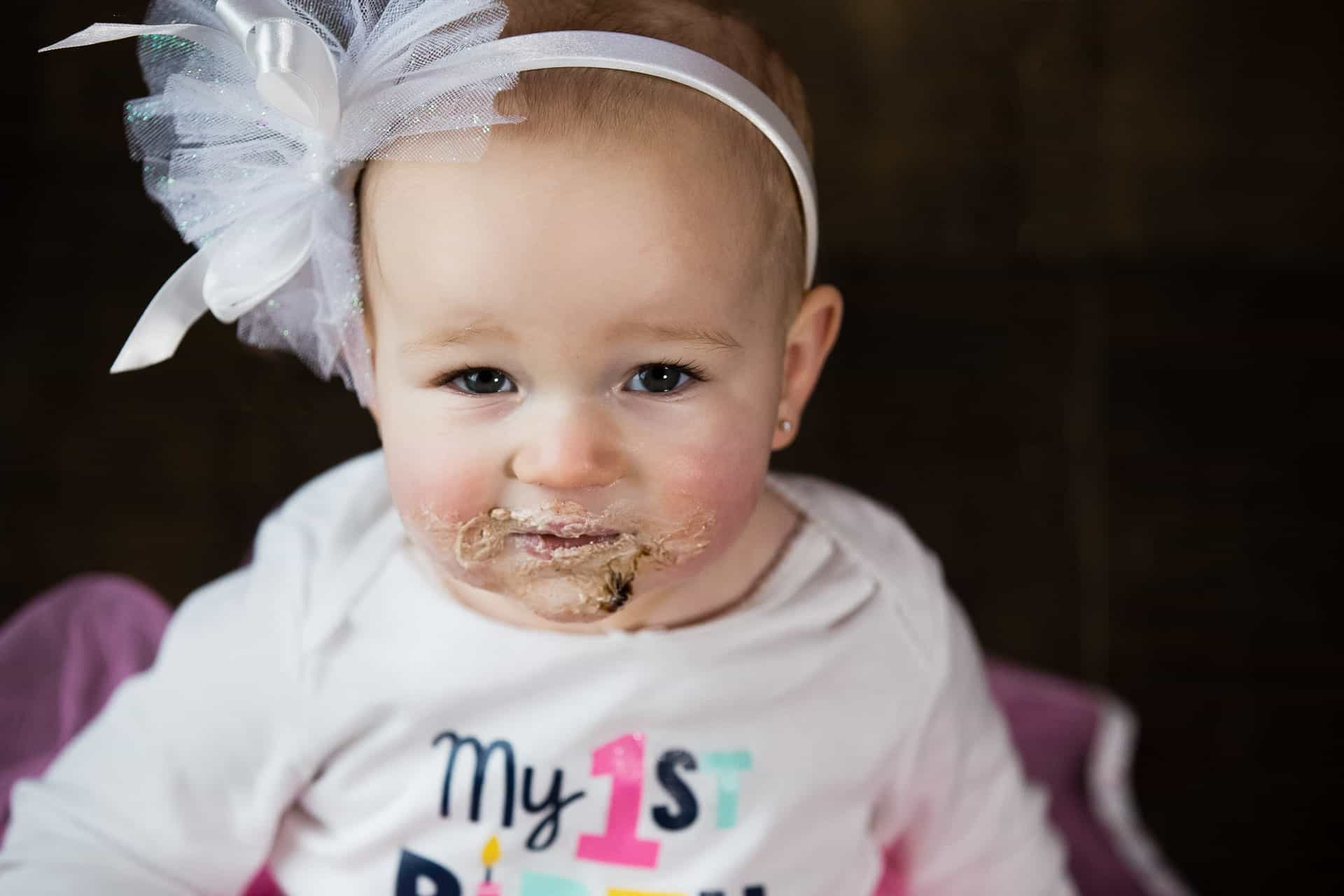Baby girl looking at camera with chocolate all over her face
