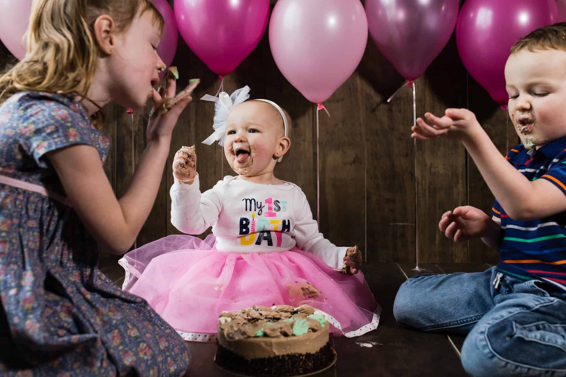 three siblings doing a cake smash together in front of pink balloons
