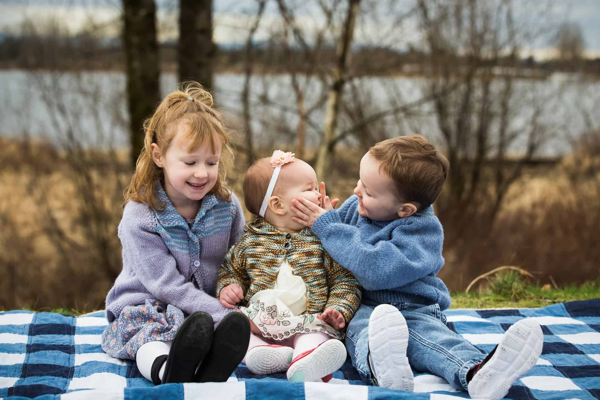 Three kids on blanket by river with brother squishing baby sister's cheeks