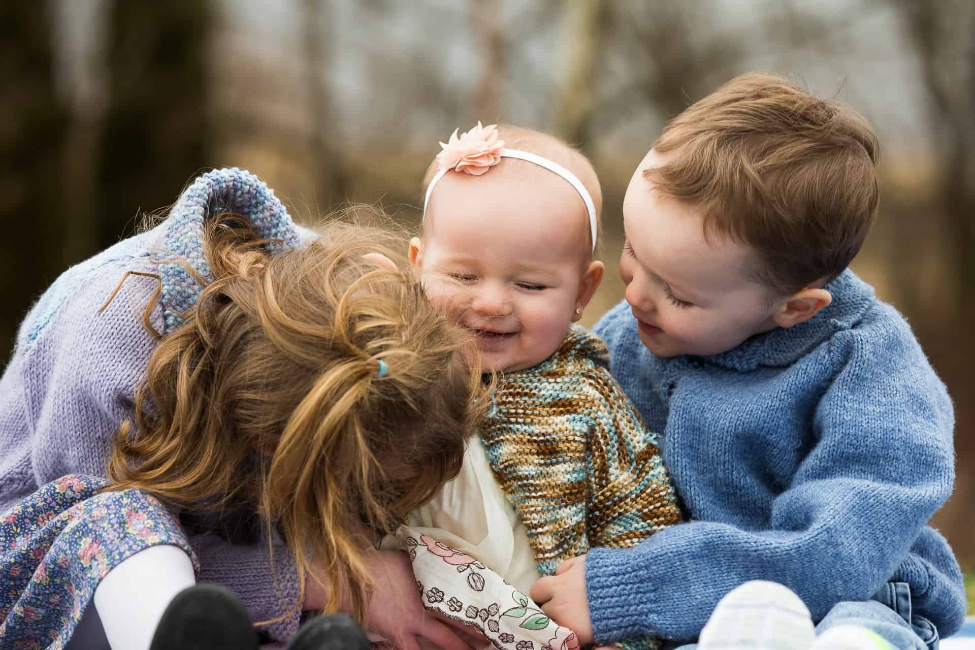 Three children hugging and laughing together