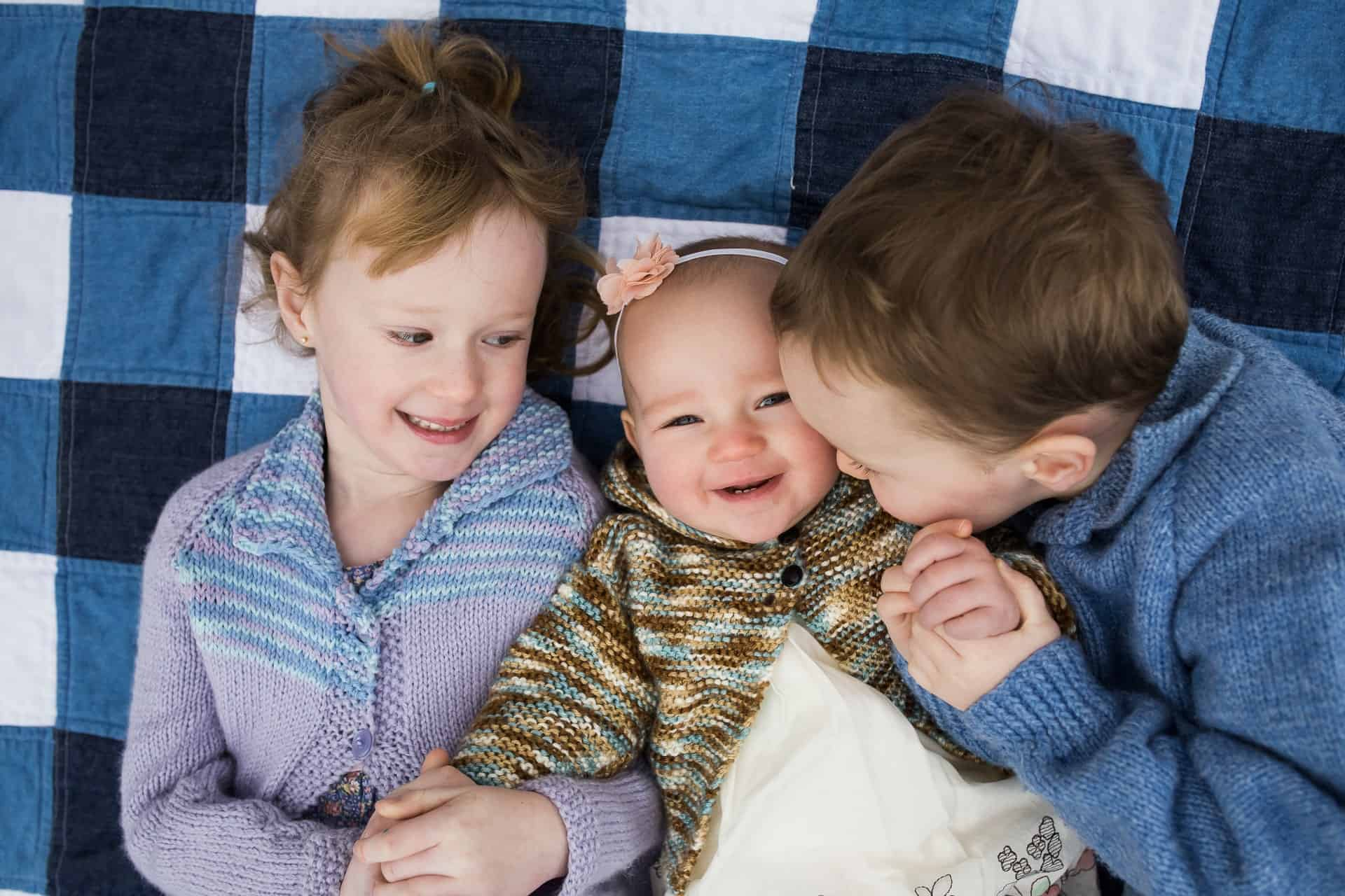 three siblings laying on a blanket holding hands and smiling