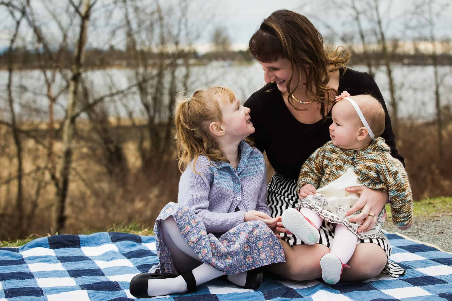mother and two daughters sitting on a blanket by a river smiling at each other