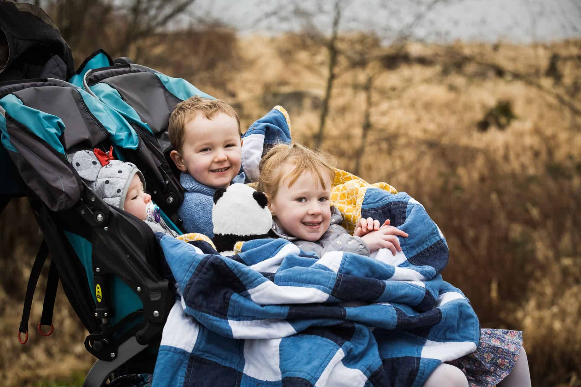 three siblings piled on top of each other in a stroller under a blanket
