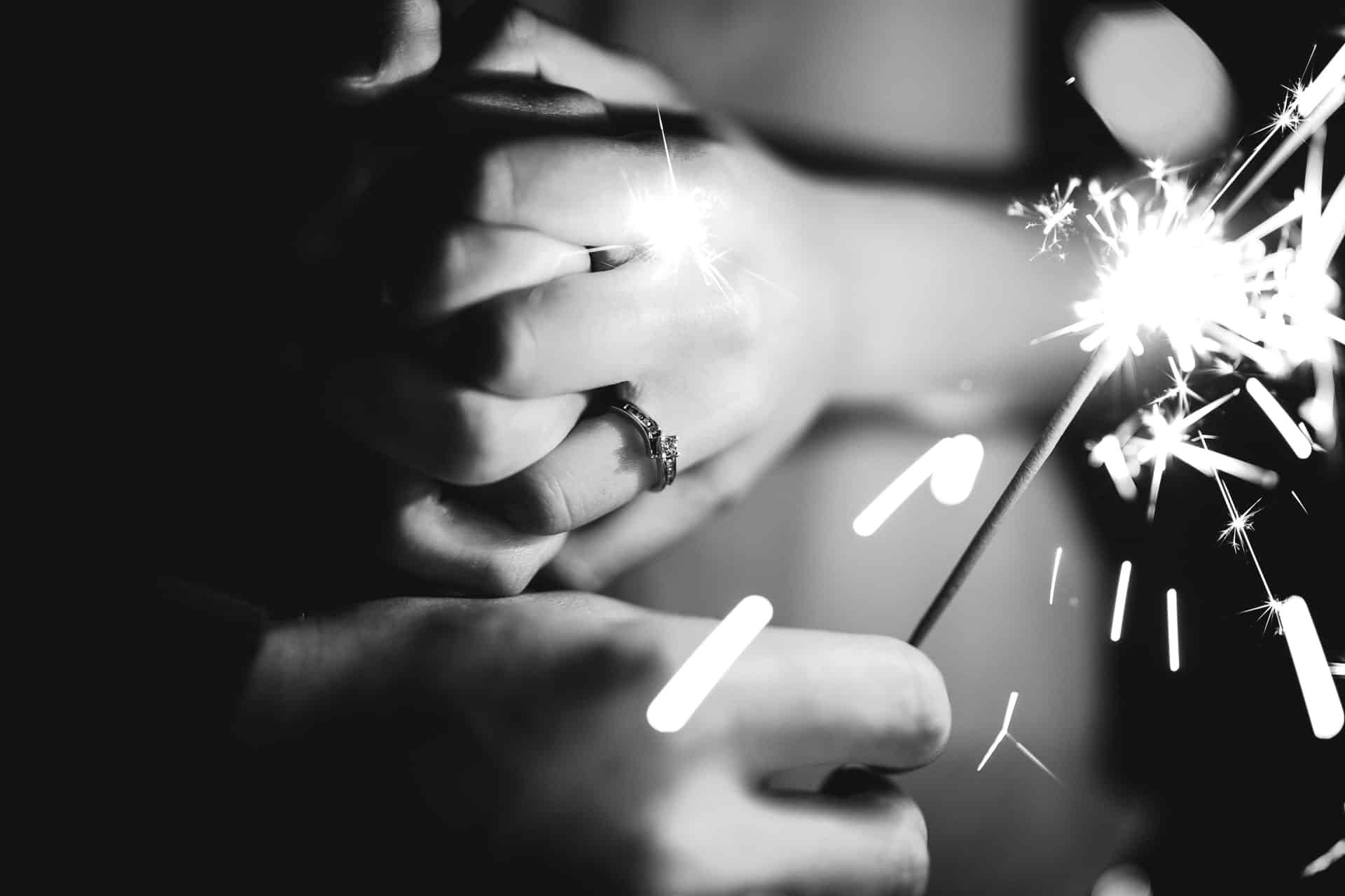 black and white image of holding hands with a sparkler illuminating an engagement ring