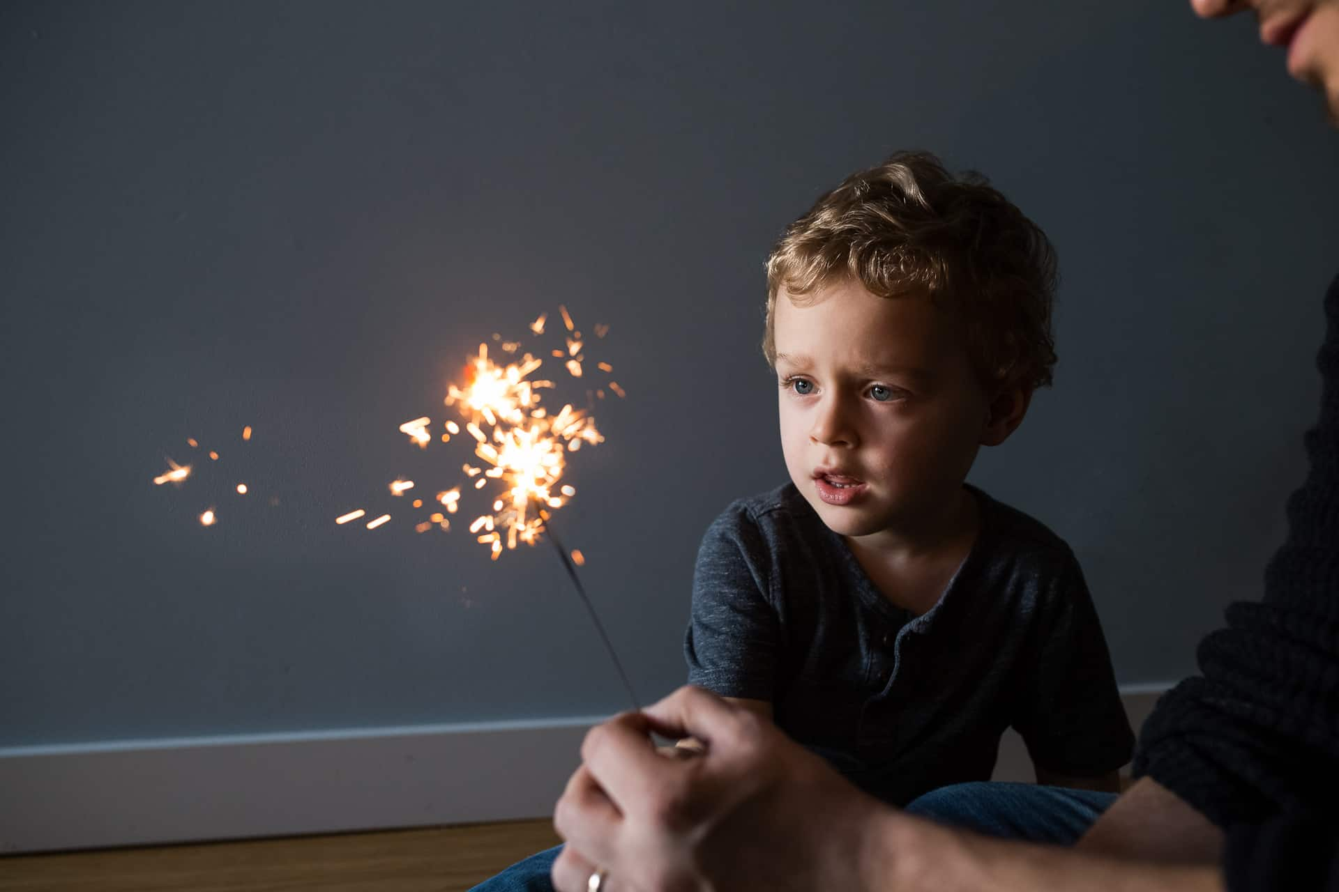 toddler boy looking at sparkler