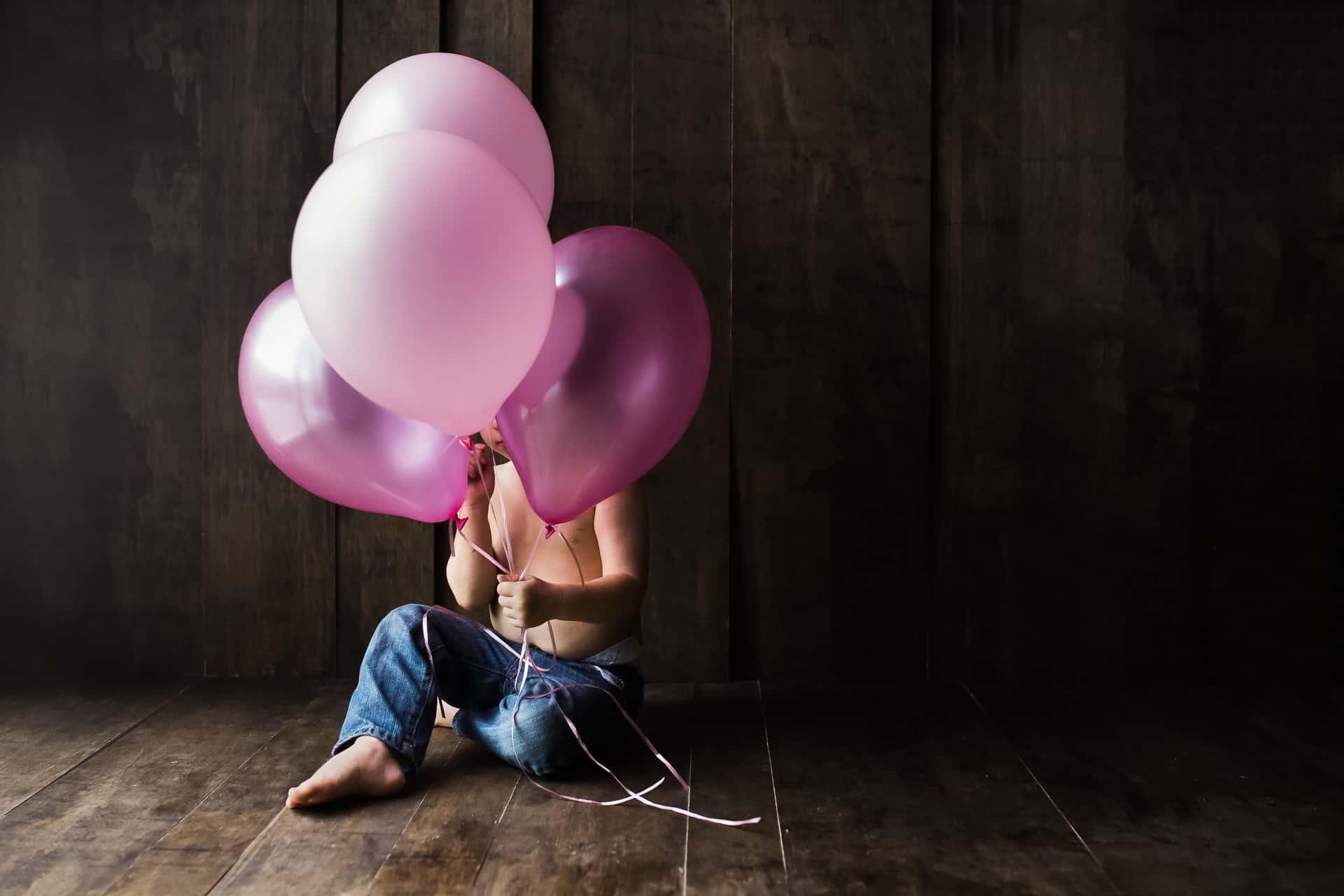 toddler boy holding pink balloons