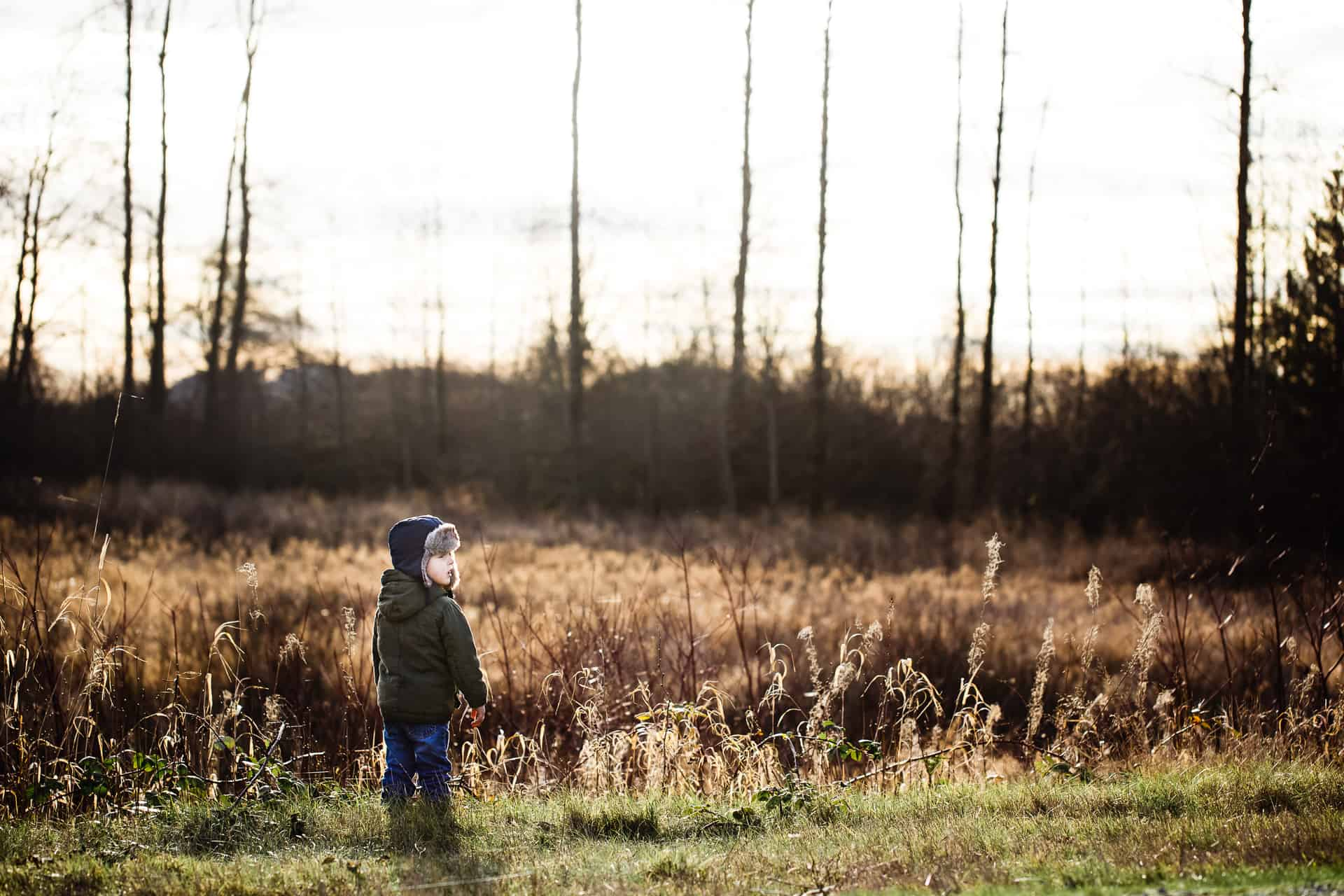 toddler boy in winter gear standing at edge of a field