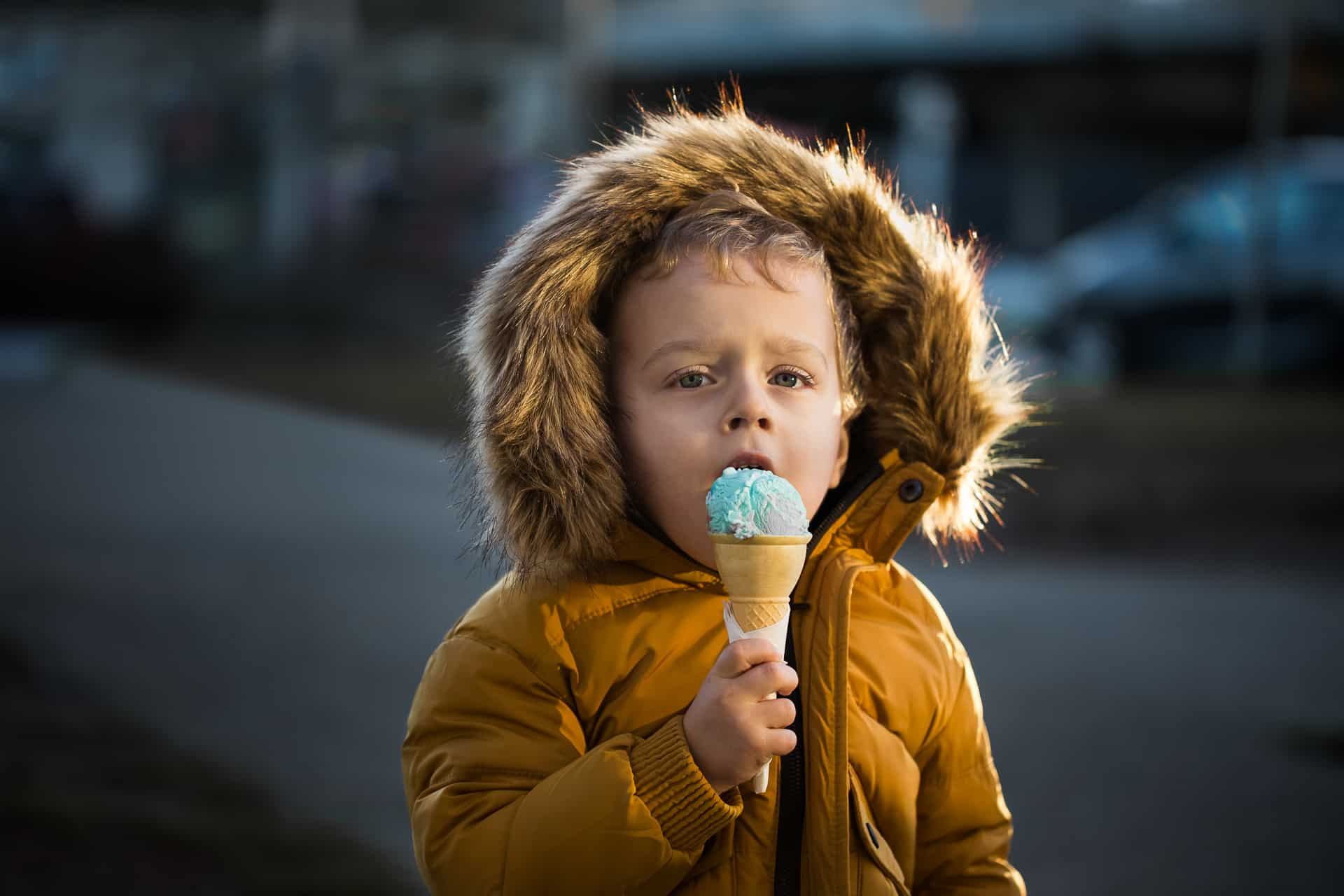 toddler boy with winter jacket eating ice cream cone