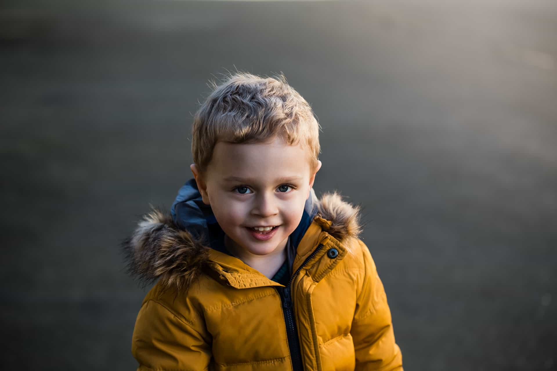 toddler boy in mustard yellow winter coat smiling