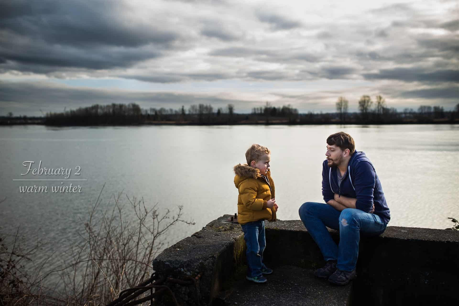 toddler boy standing the a river with his dad talking