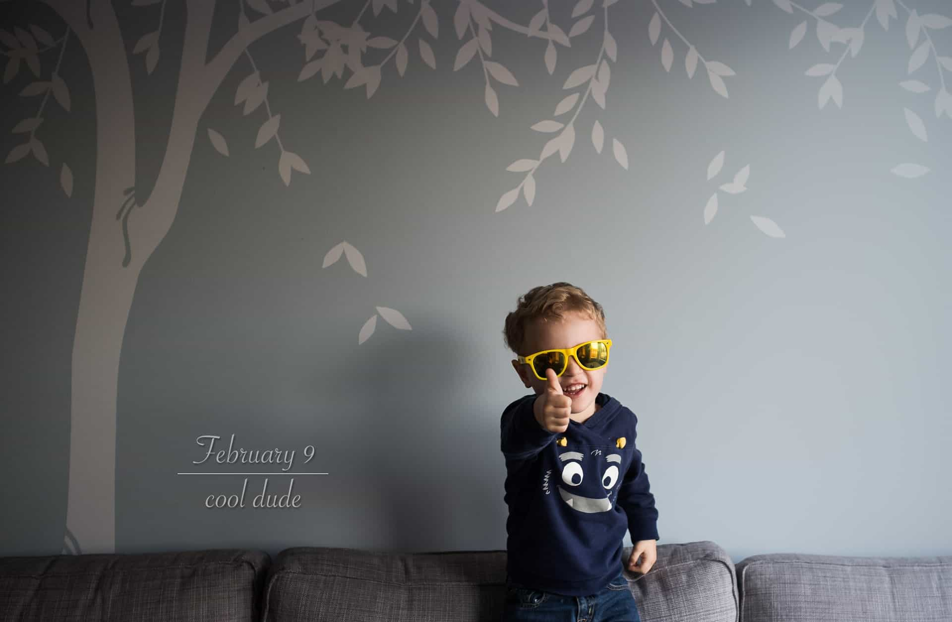 toddler boy with sunglasses on smiling at the camera and giving a thumbs up sign