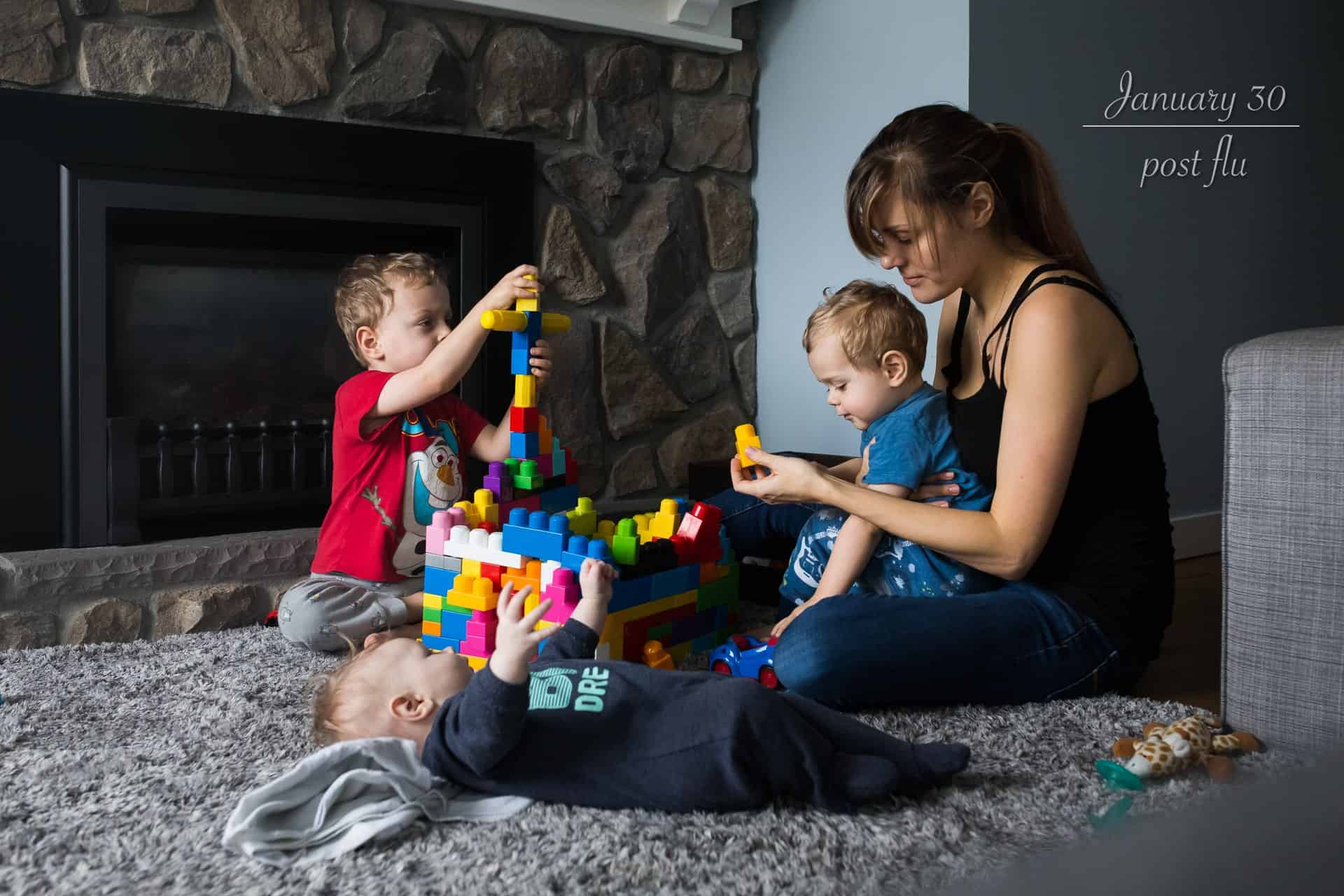 mom playing blocks with her two toddler sons while a newborn lays on the floor beside them watching