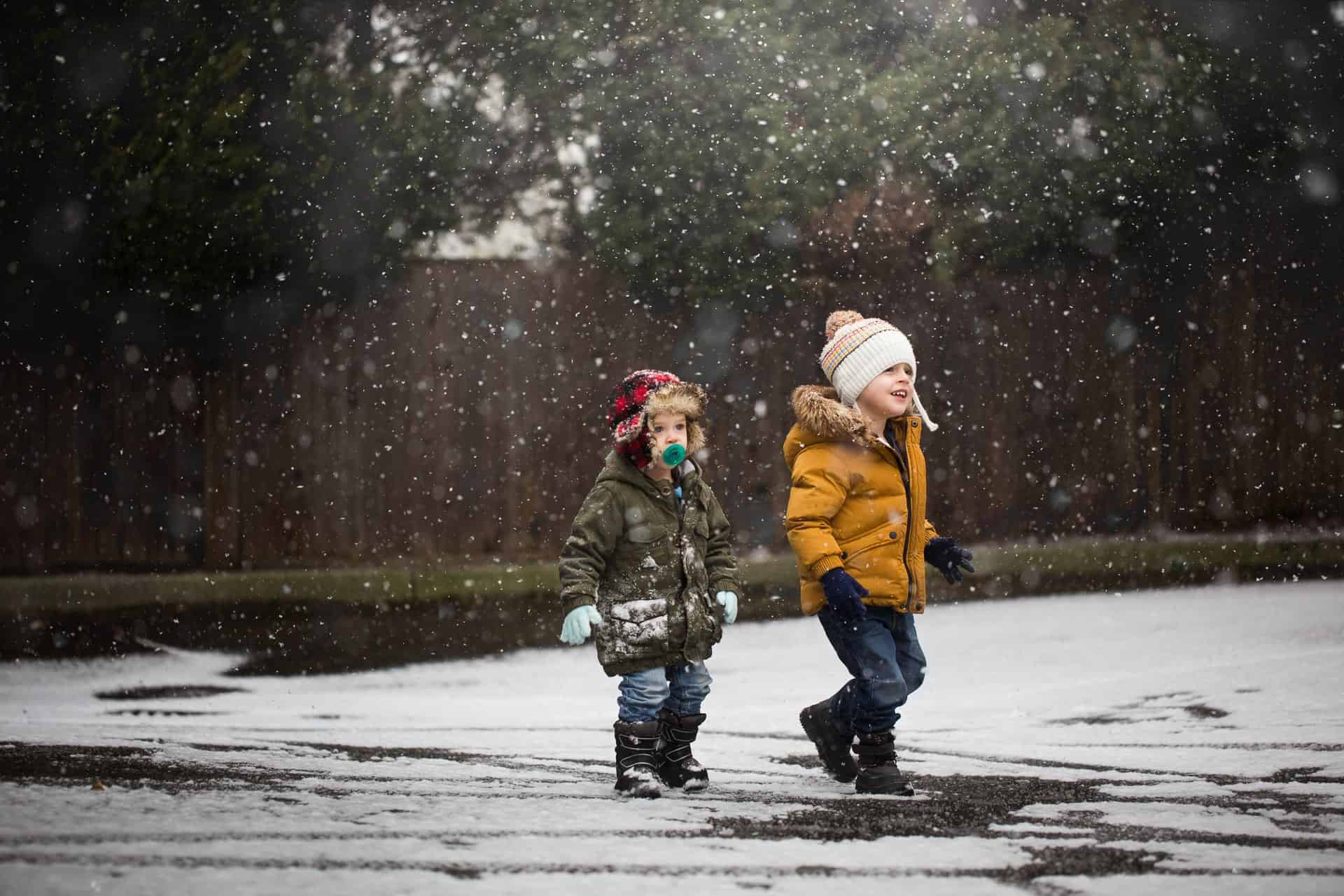 two toddler boys in snow gear walking and smiling while they play in the snow