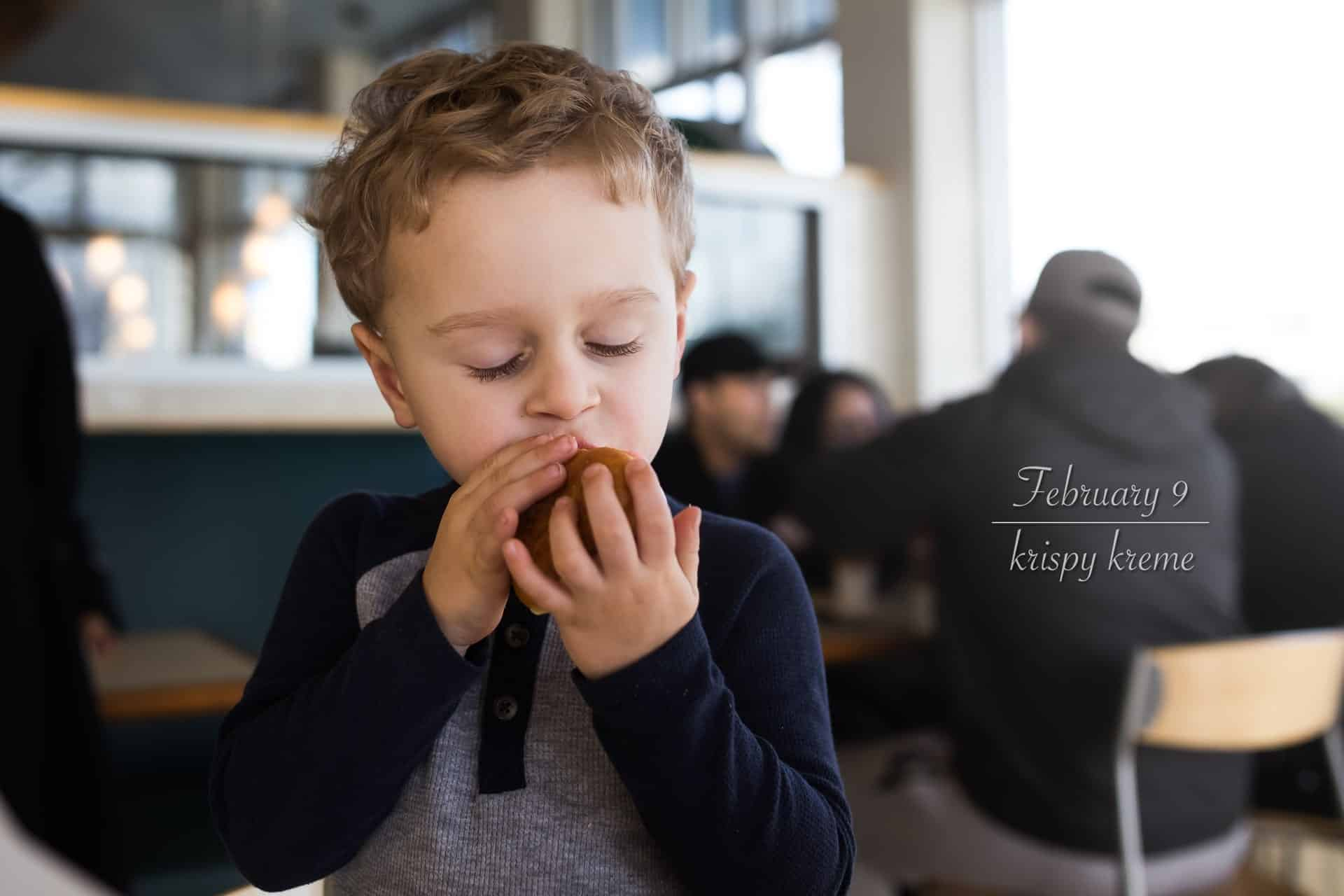 toddler boy with eyes closed taking a big bite of a krispy kreme donut