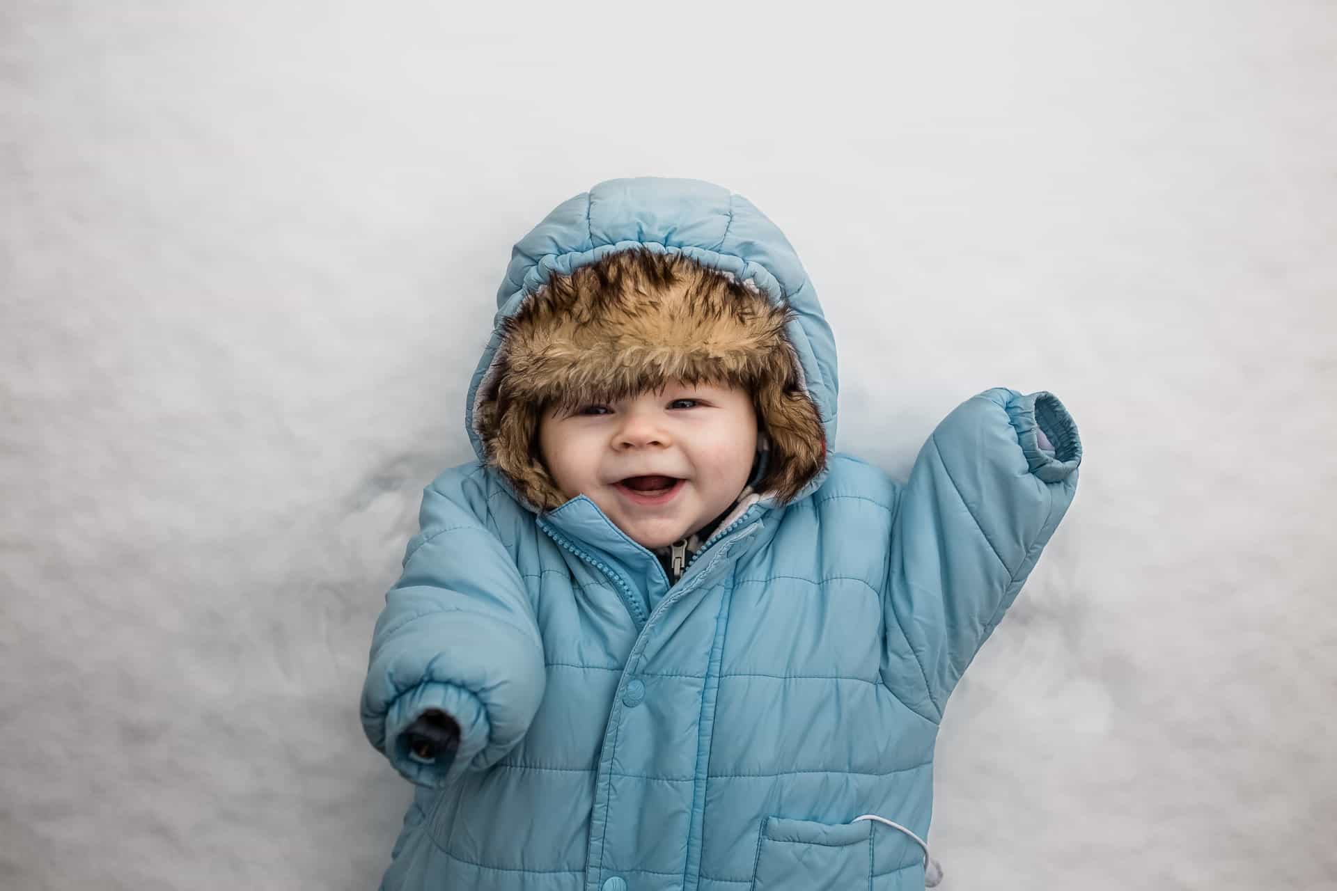 baby in snowsuit and furry hat laying in the snow smiling