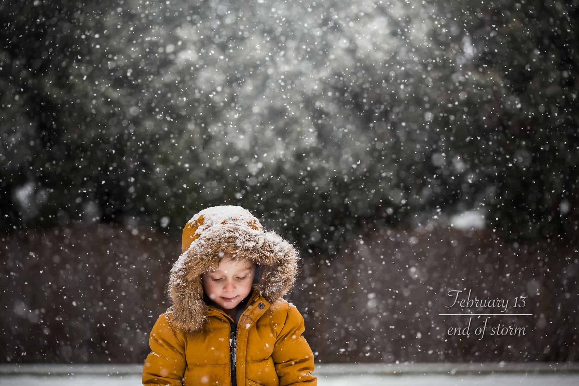 boy in yellow coat and fur lined hood in snowy forest