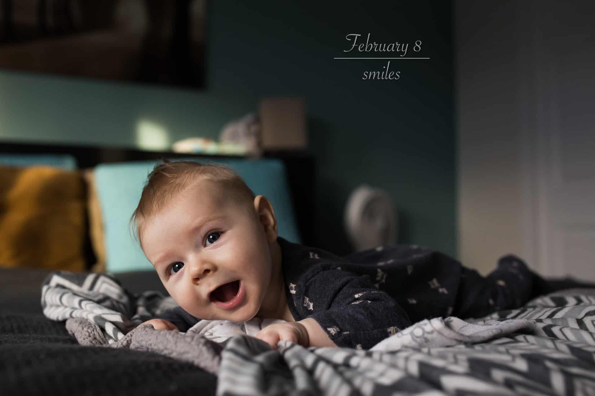baby laying on a large bed smiling at the camera during tummy time