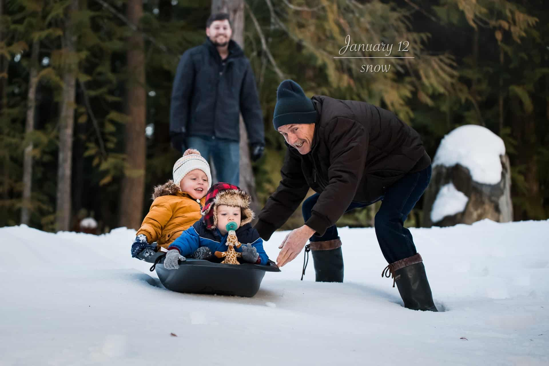 two toddlers sledding down a snowy hill while grandpa pushes them and dad smiles in the background