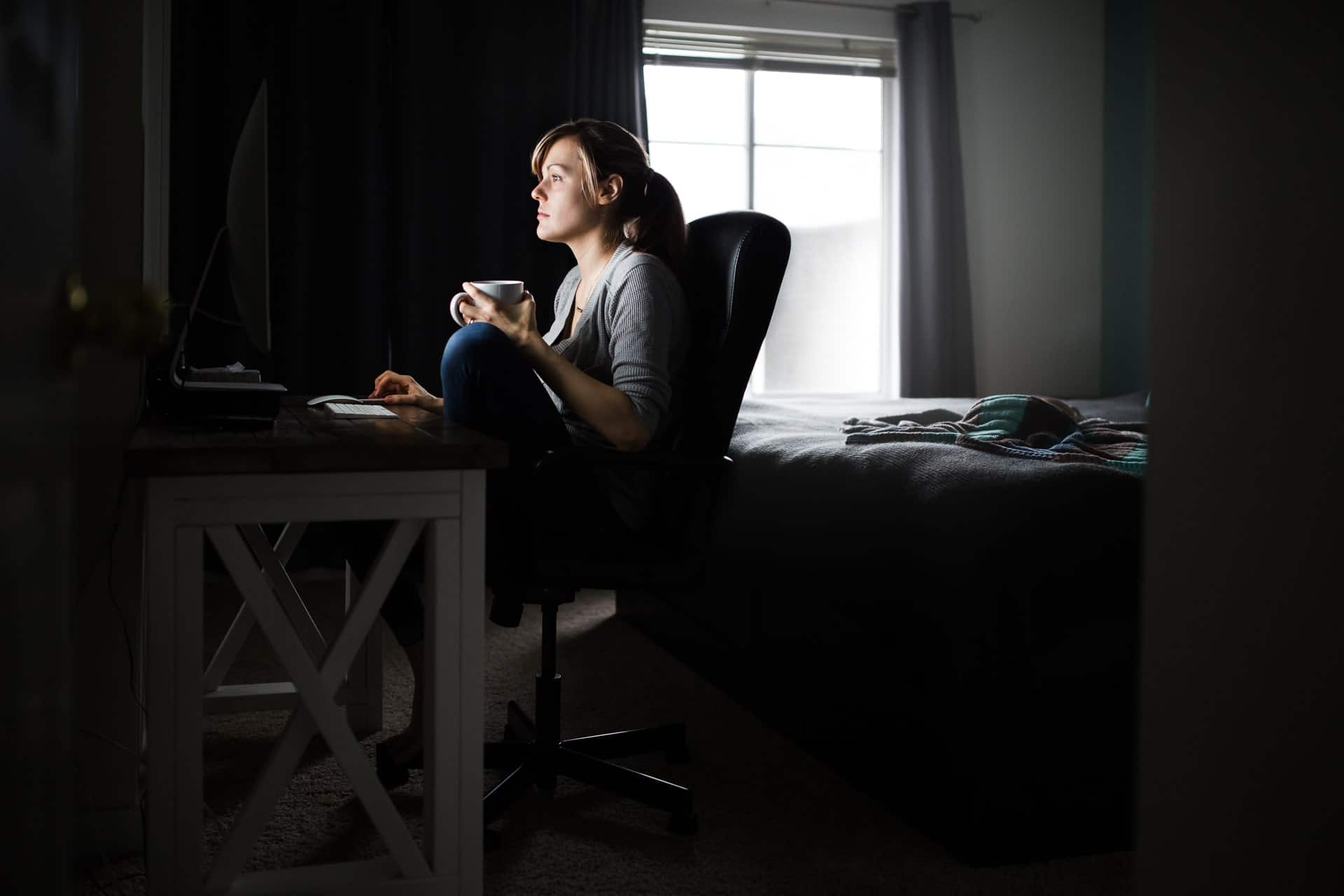 mom sitting at computer with coffee with newborn sleeps on the bed behind her