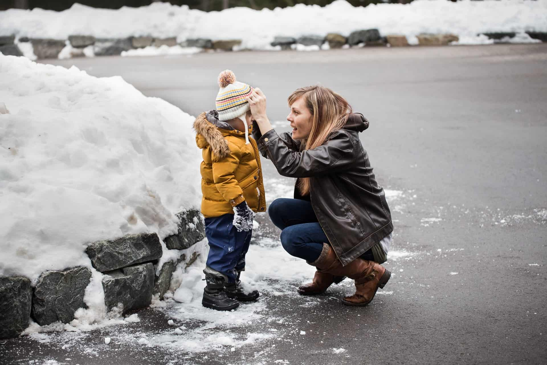 mom kneeling in front of toddler and adjusting his toque in the snow