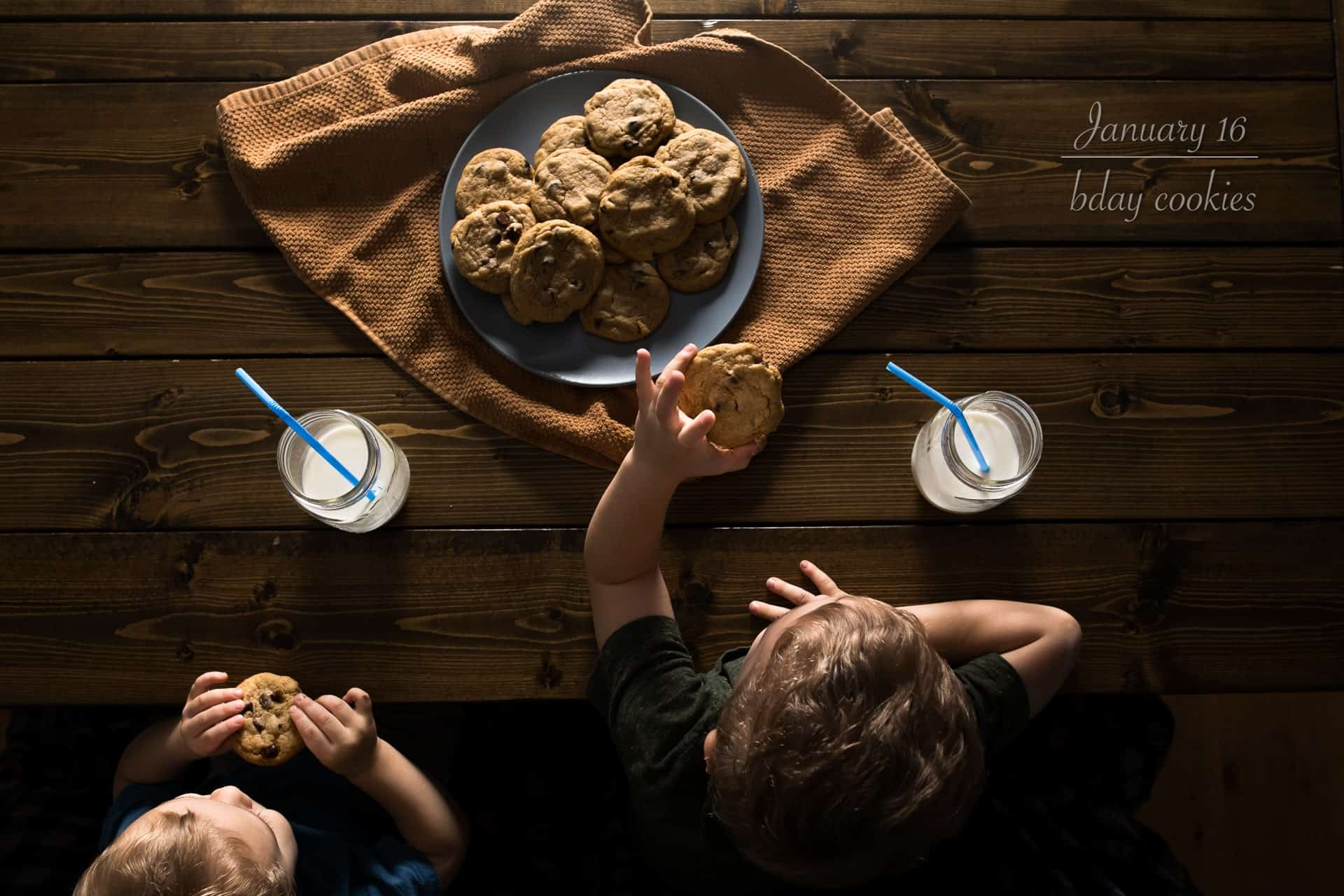 two boys sitting at table eating cookies and milk