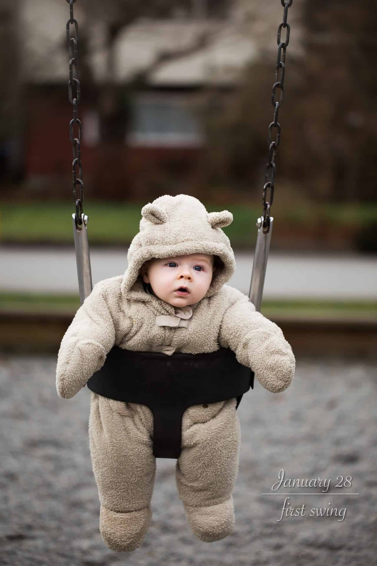 baby boy in bear snow suit in a playground swing