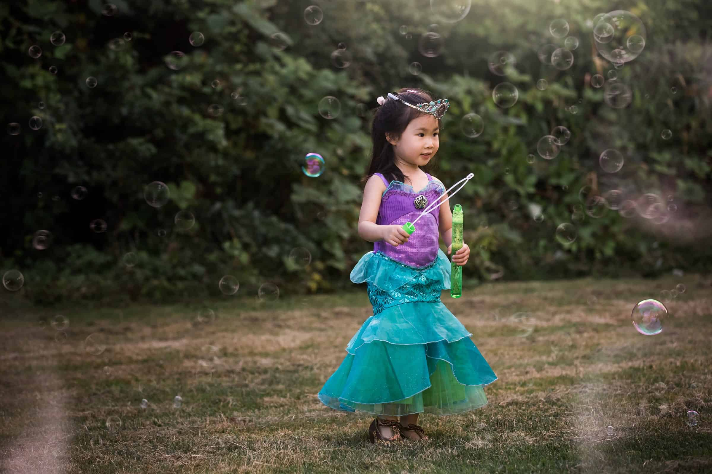 little girl dressed as Princess Ariel blowing bubbles