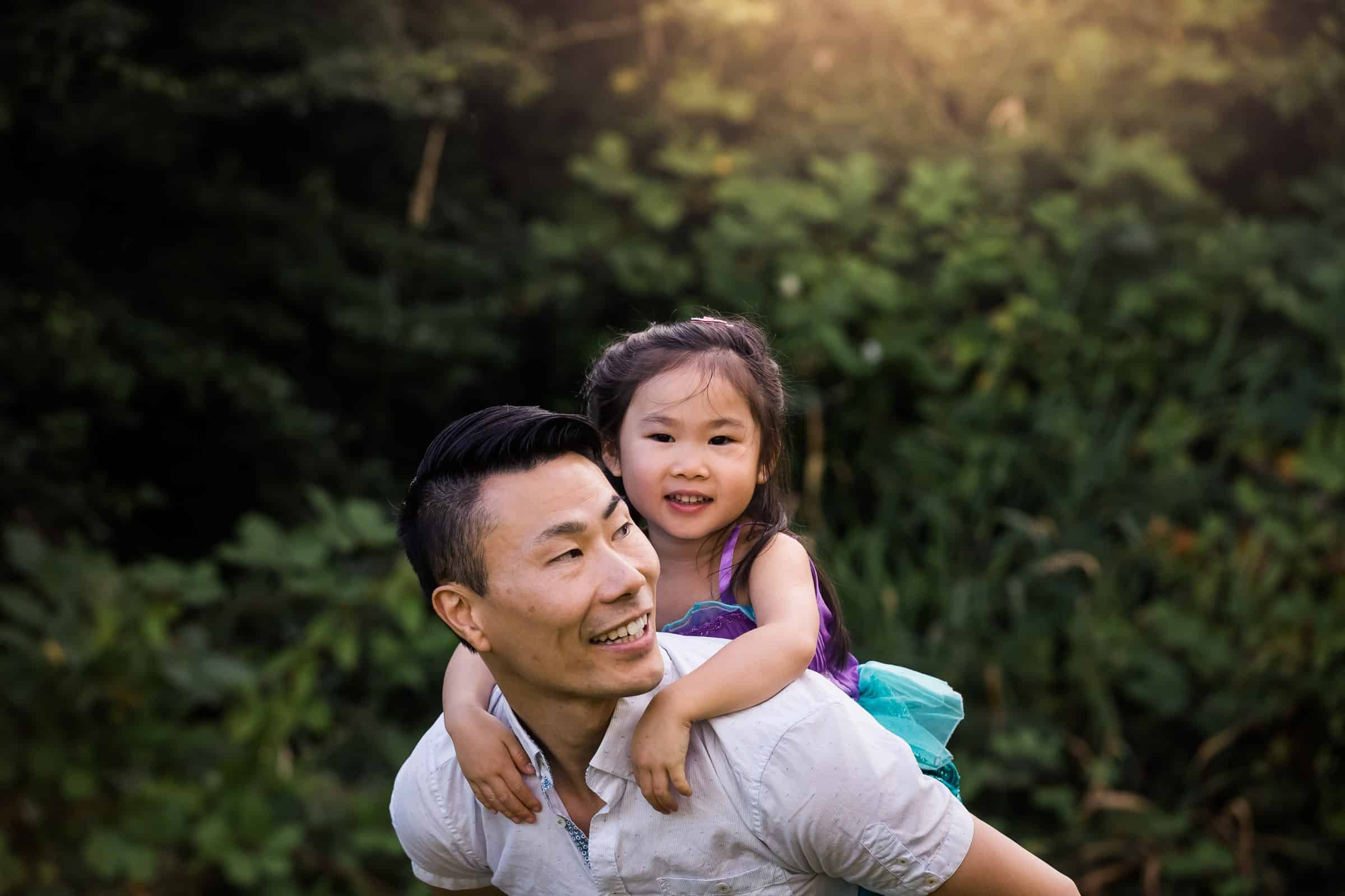 little girl on her dad's back smiling at the camera