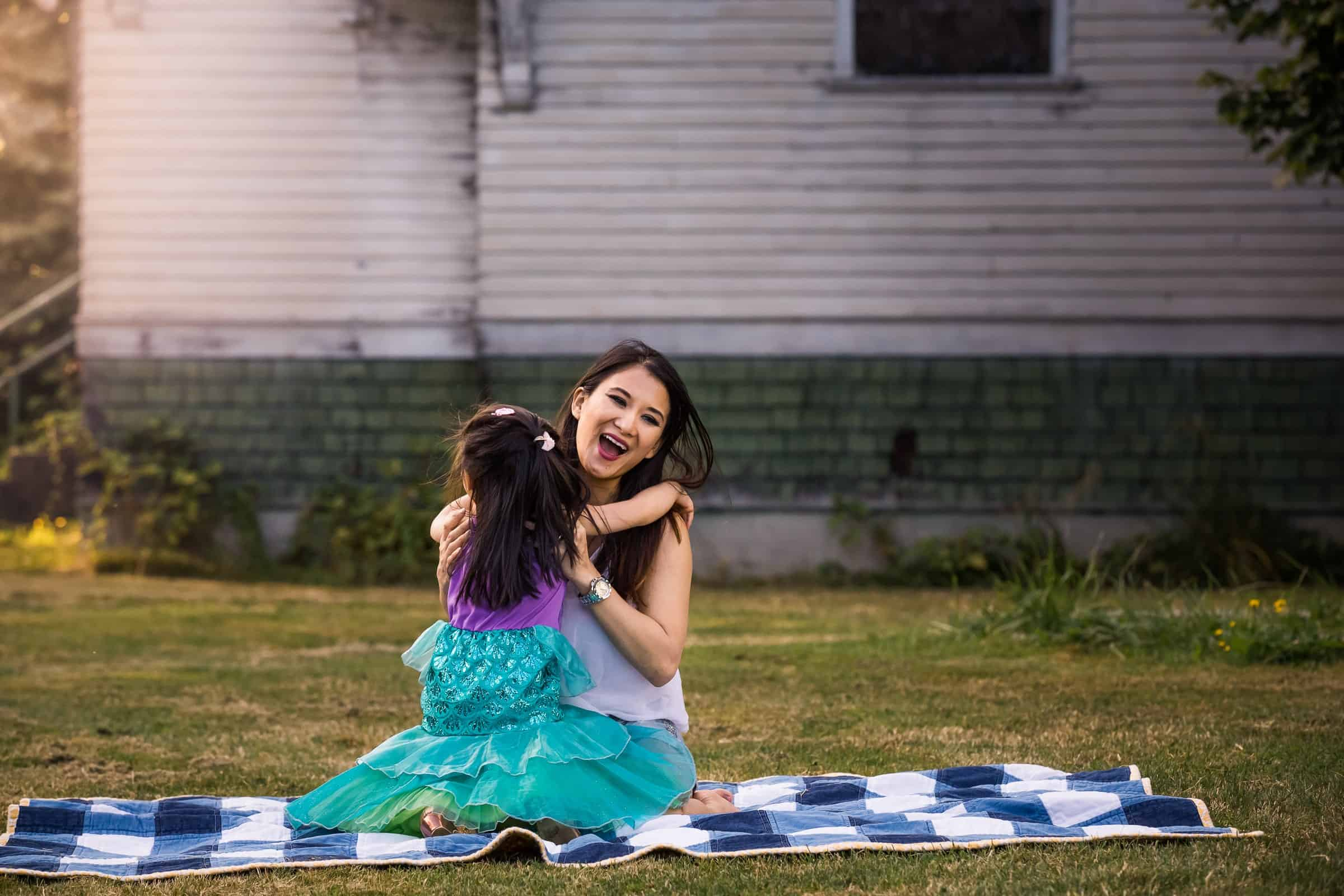 little girl hugging her laughing mom on a blanket