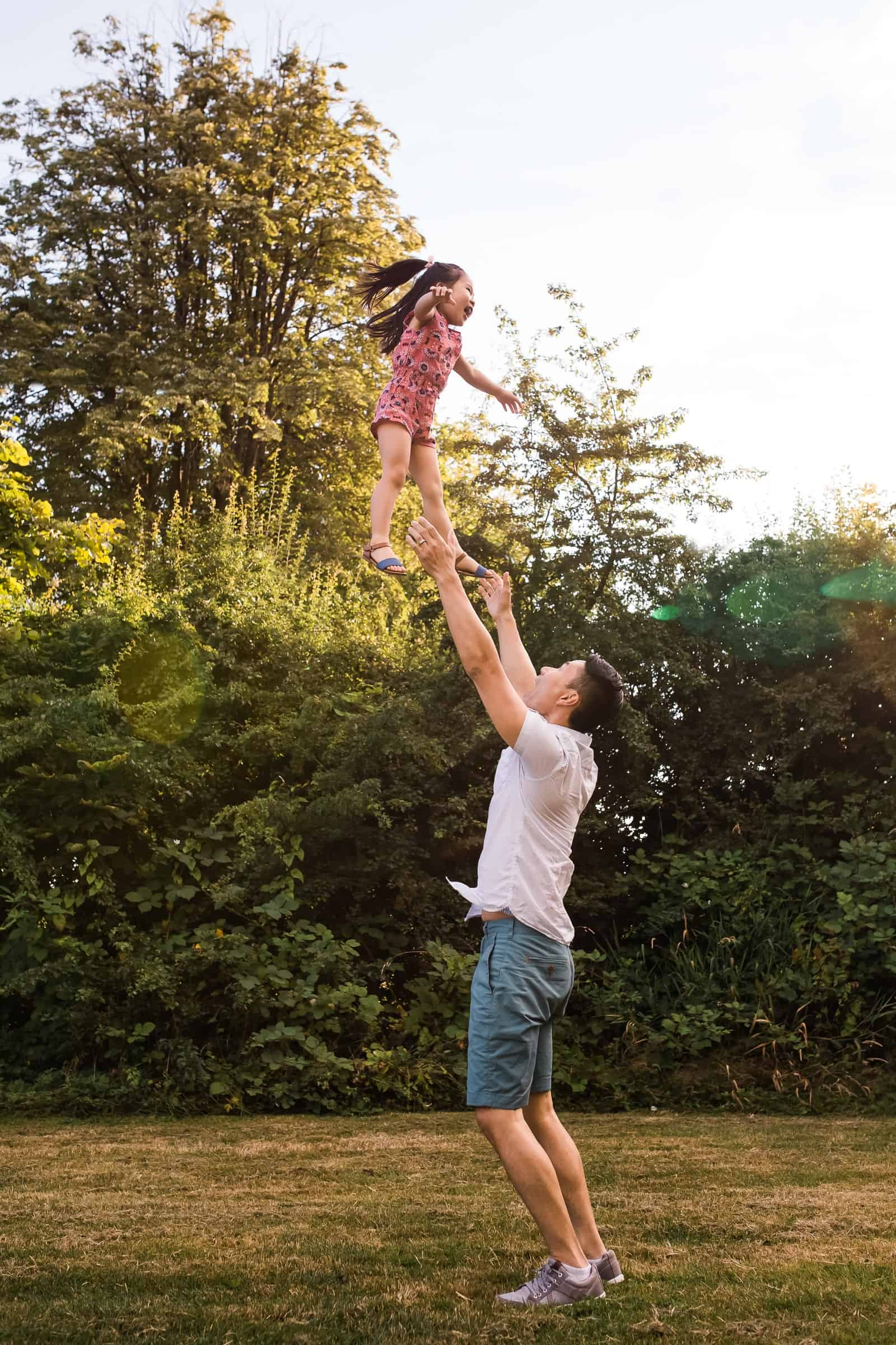 dad throwing little girl up into the air