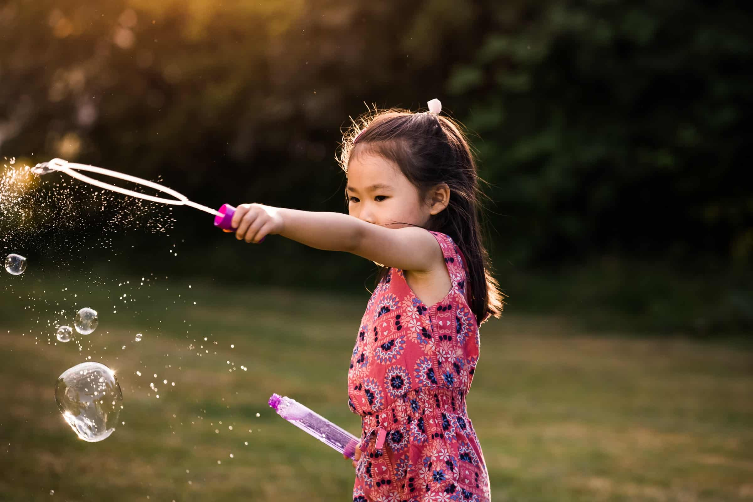 little girl making bubbles in the sunset
