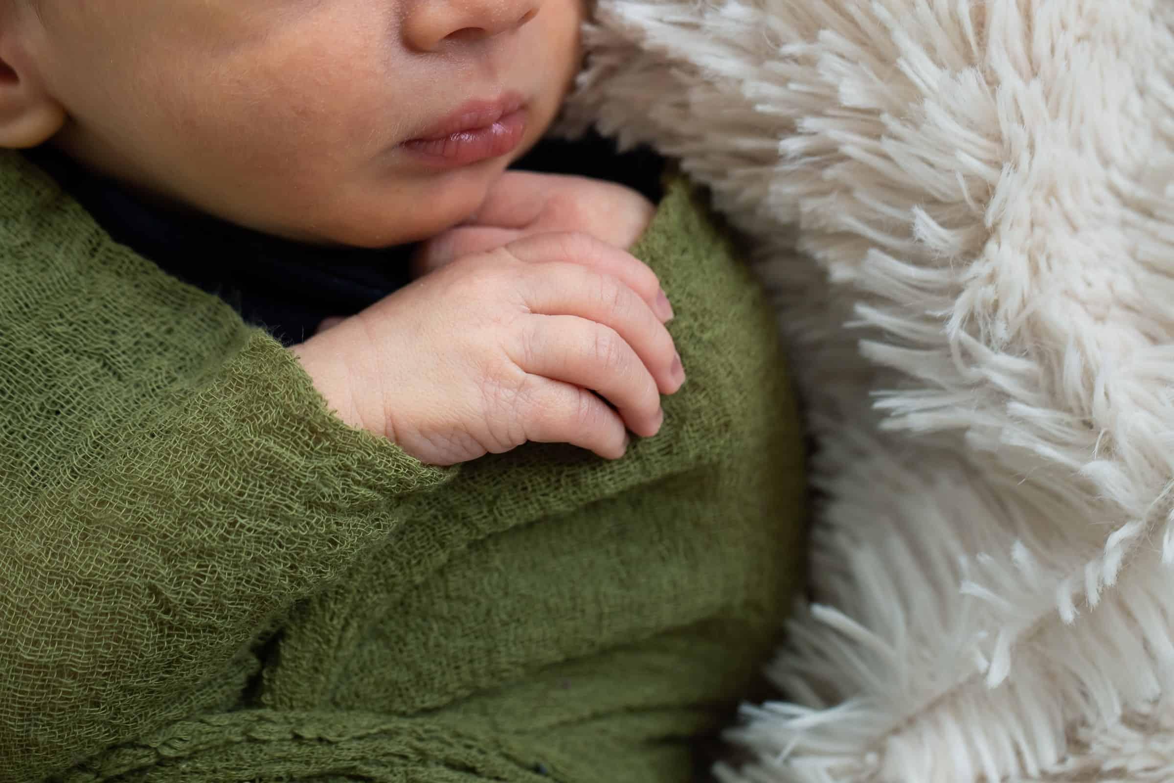 close up of sleeping newborn hand and lips