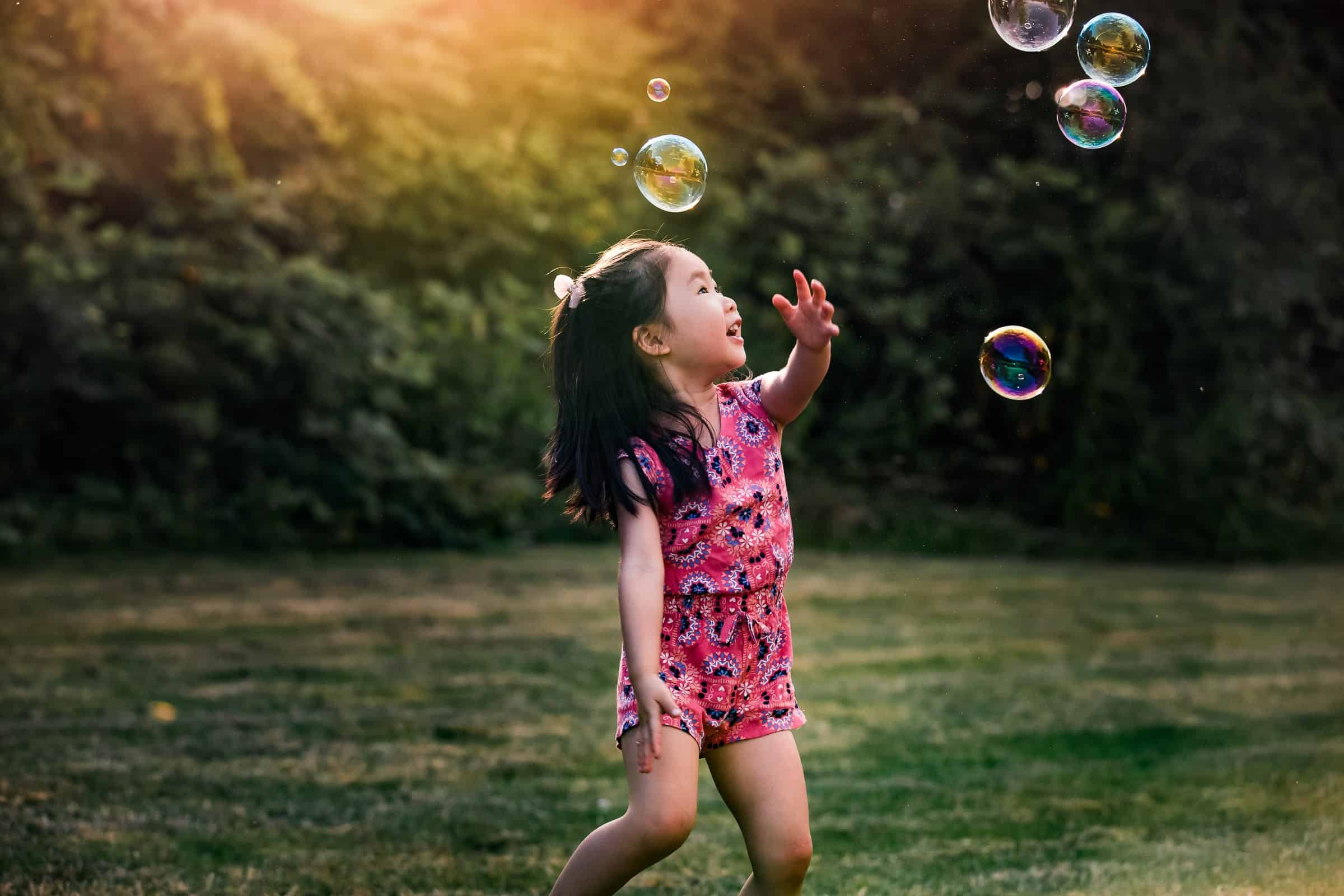 little girl chasing bubbles in the sunset