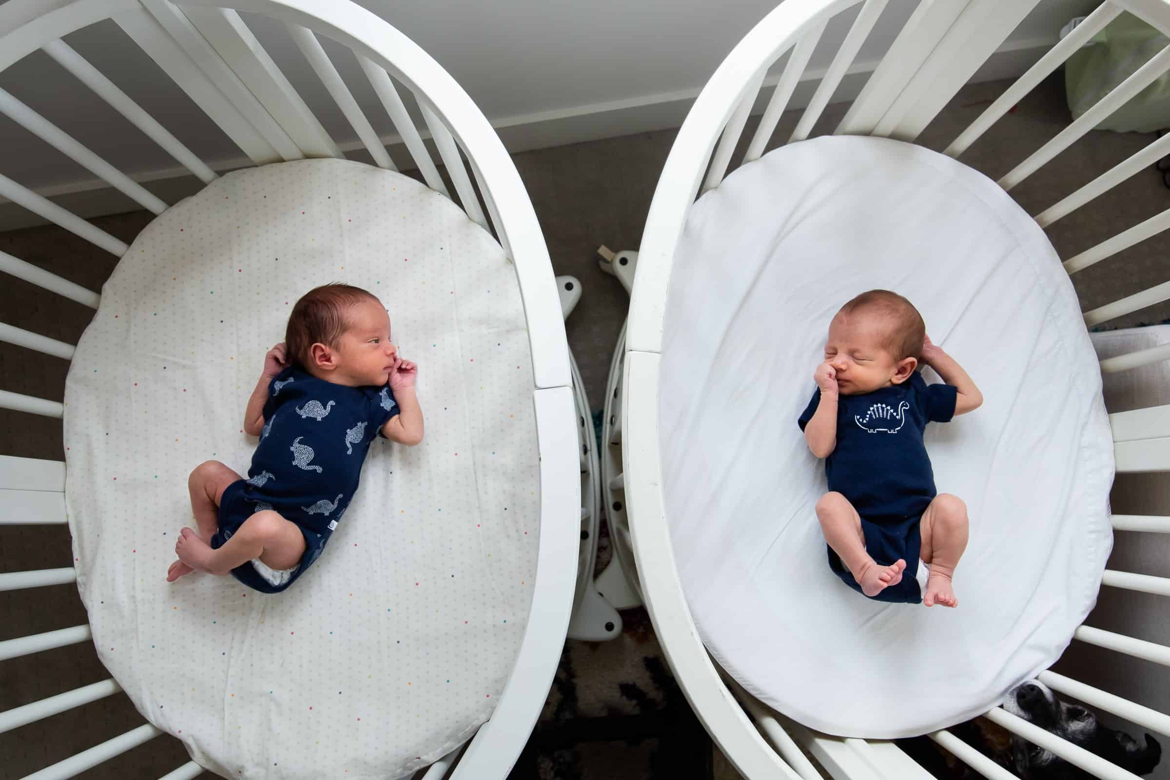 newborn twins in cribs side by side from above