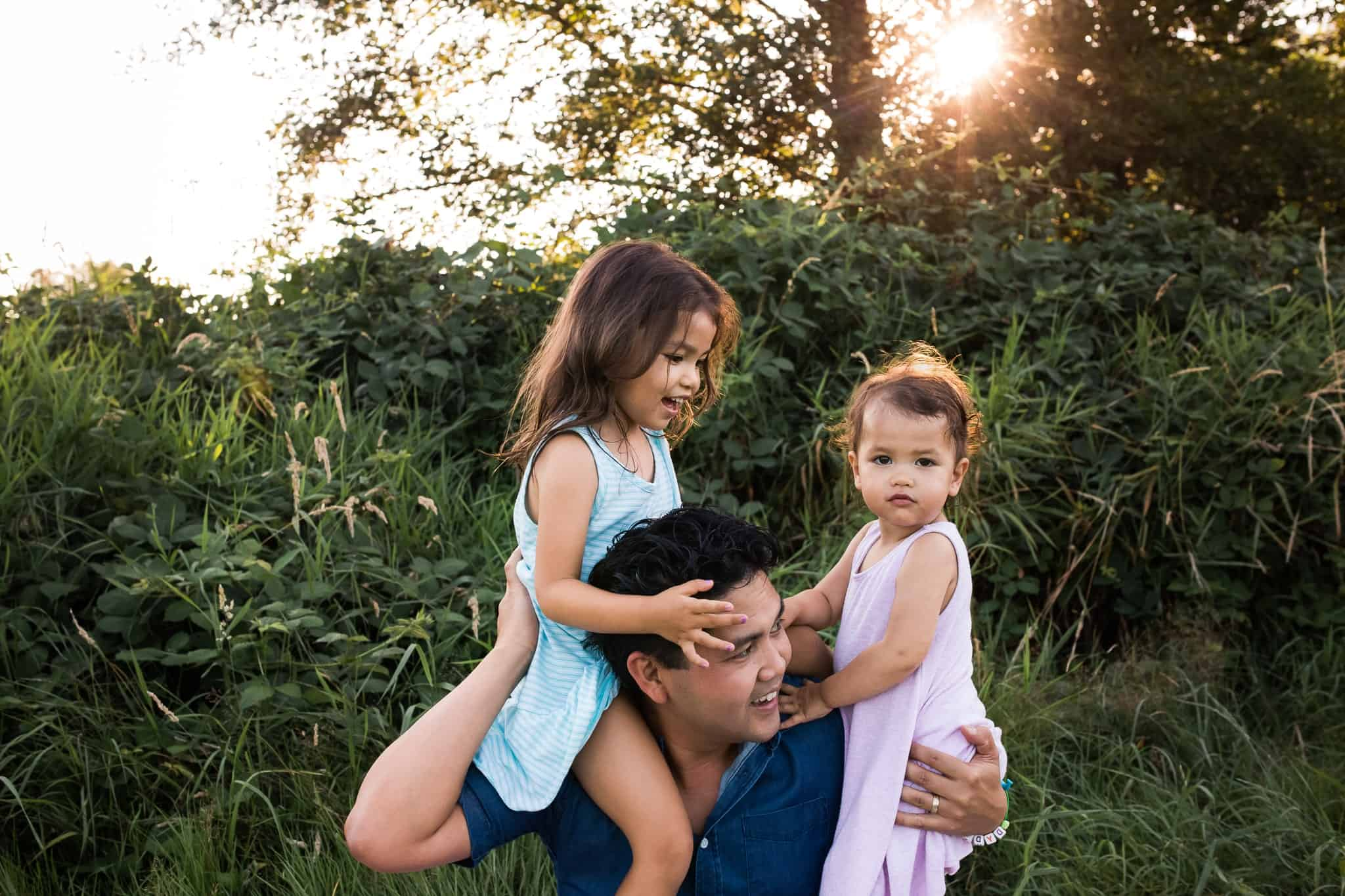 dad holding his two daughters on his shoulders