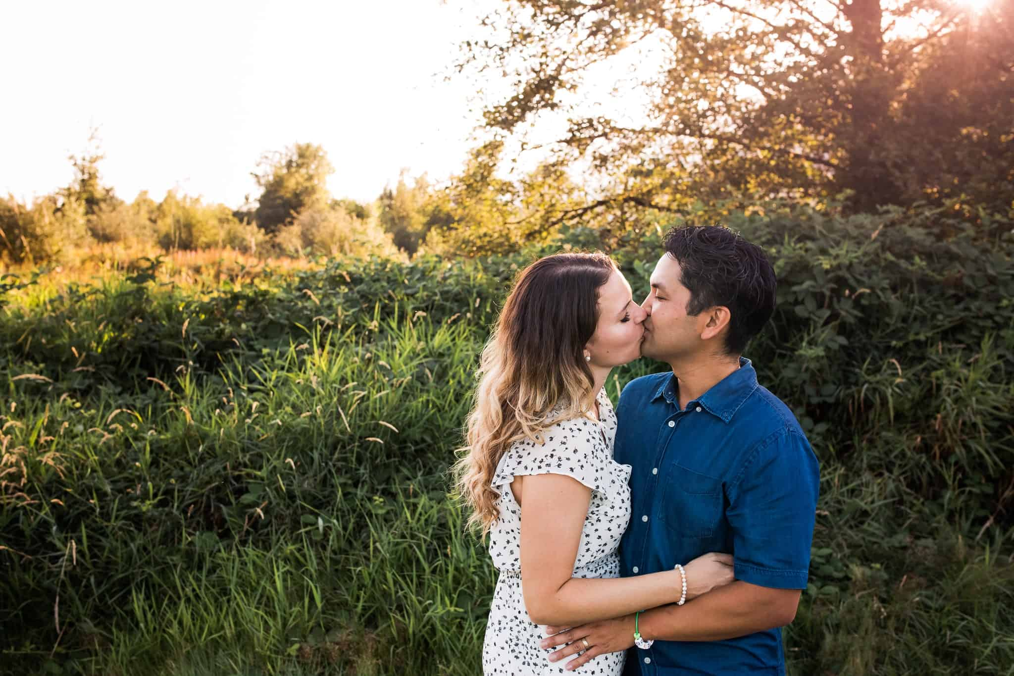 couple kissing with sunflare and field behind them
