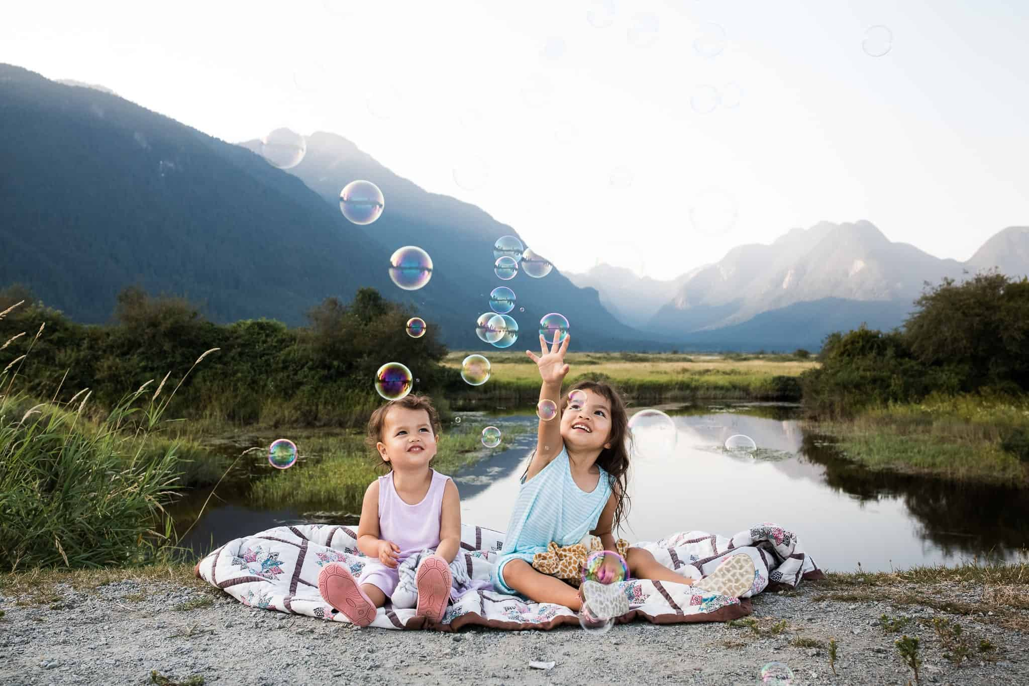 little girls sitting on blanket catching bubbles with lake and mountains behind them