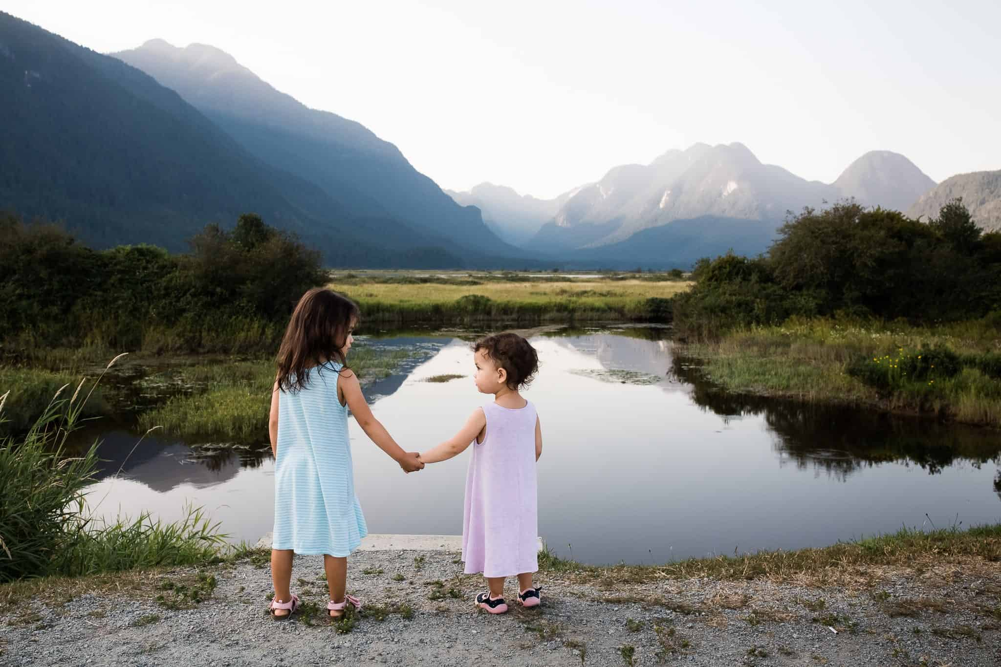 two little girls holding hands with lake and mountains in front of them